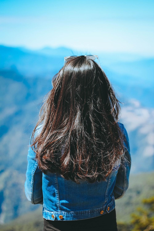 woman wearing blue denim jacket standing near mountain