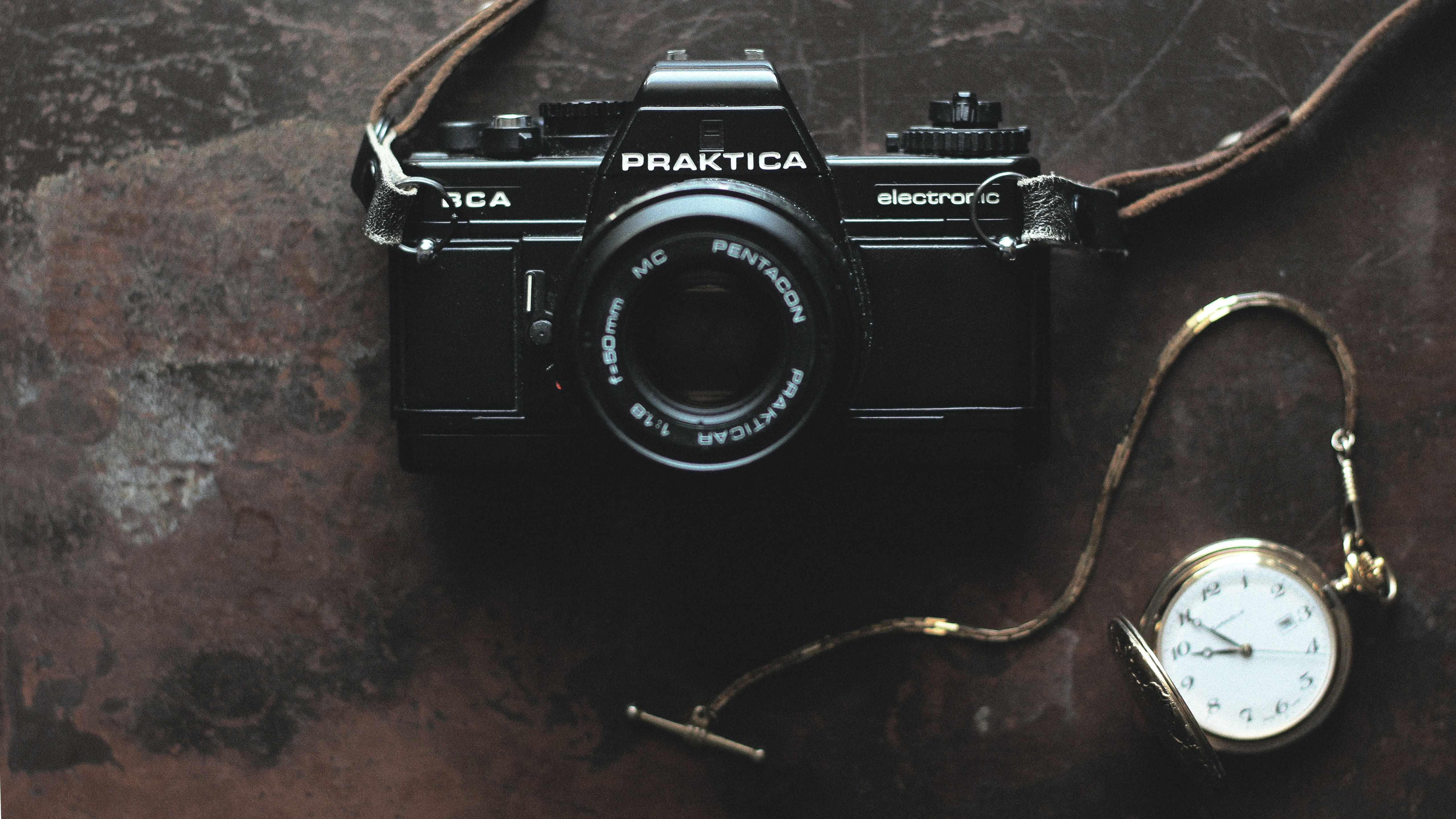 Praktica electronic vintage camera with a leather strap beside a gold pocket watch on a scratched brown surface