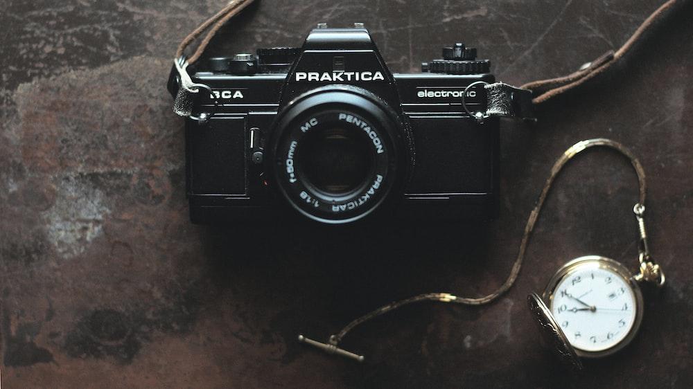 black Praktica camera and gold-colored pocket watch
