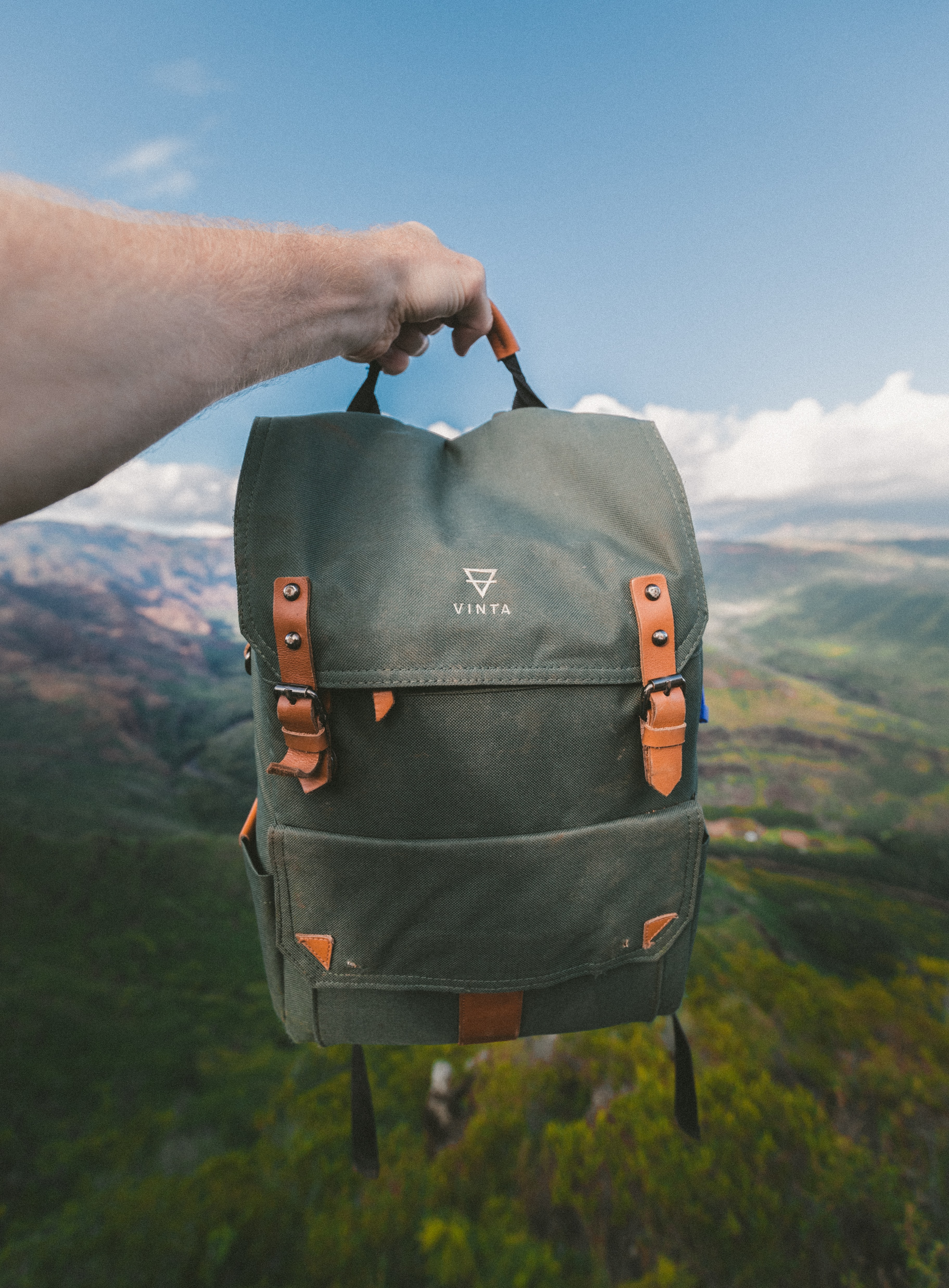 A person holds out a Vinta brand backpack against a mountainous landscape