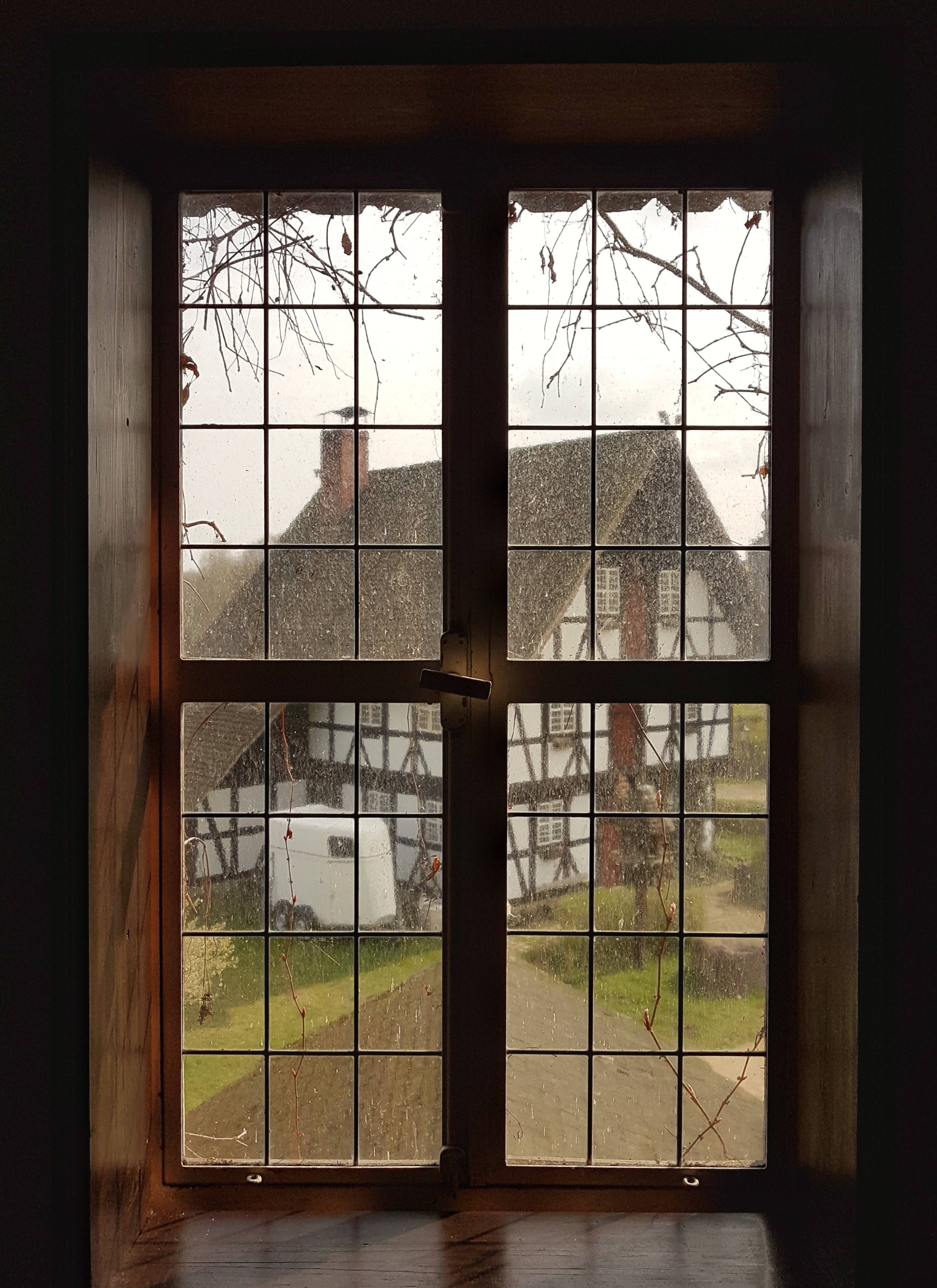 House with a wooden frame and thatched roof seen through a window of a different house