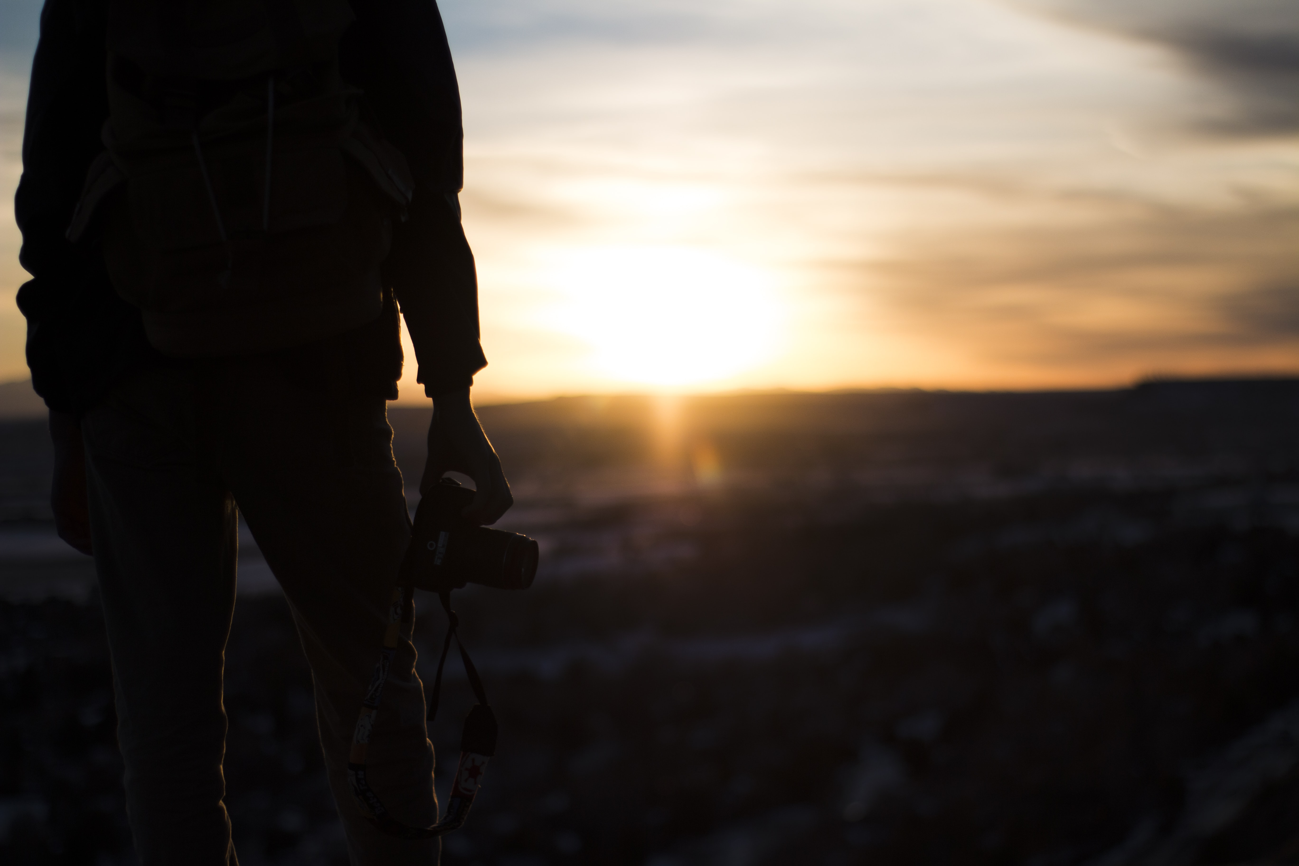 The silhouette of a photographer holding a camera during sunset or sunrise in Billings