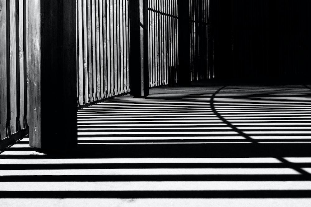 pillar of building shadows grayscale photography