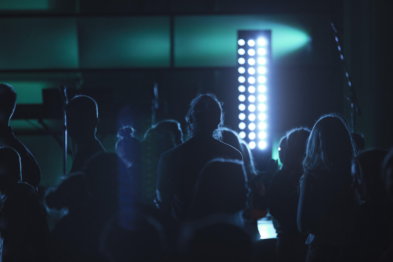 people standing near tower light inside room