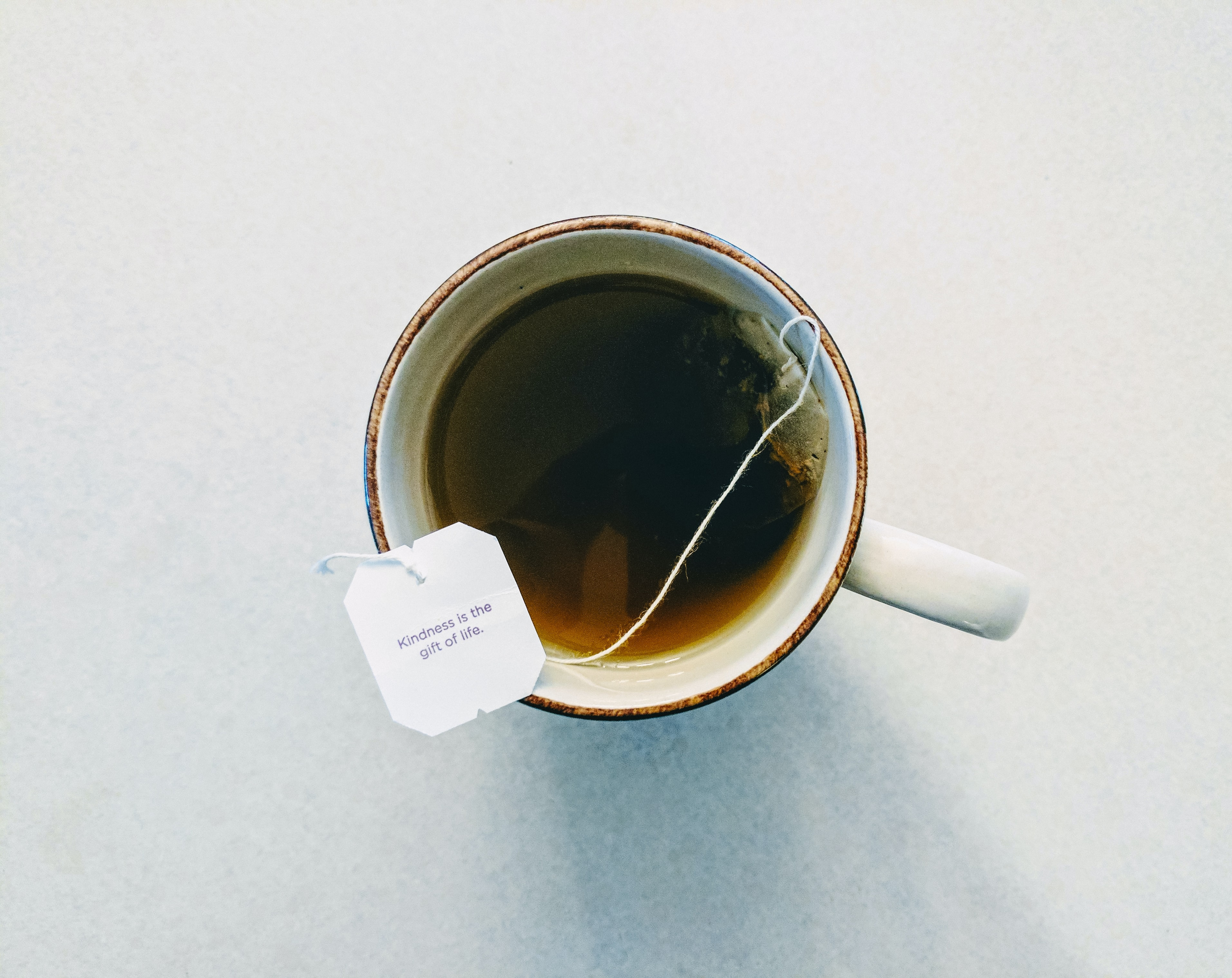 "A teabag tag with ""Kindness is the gift of life"" written on it on the edge of a mug"