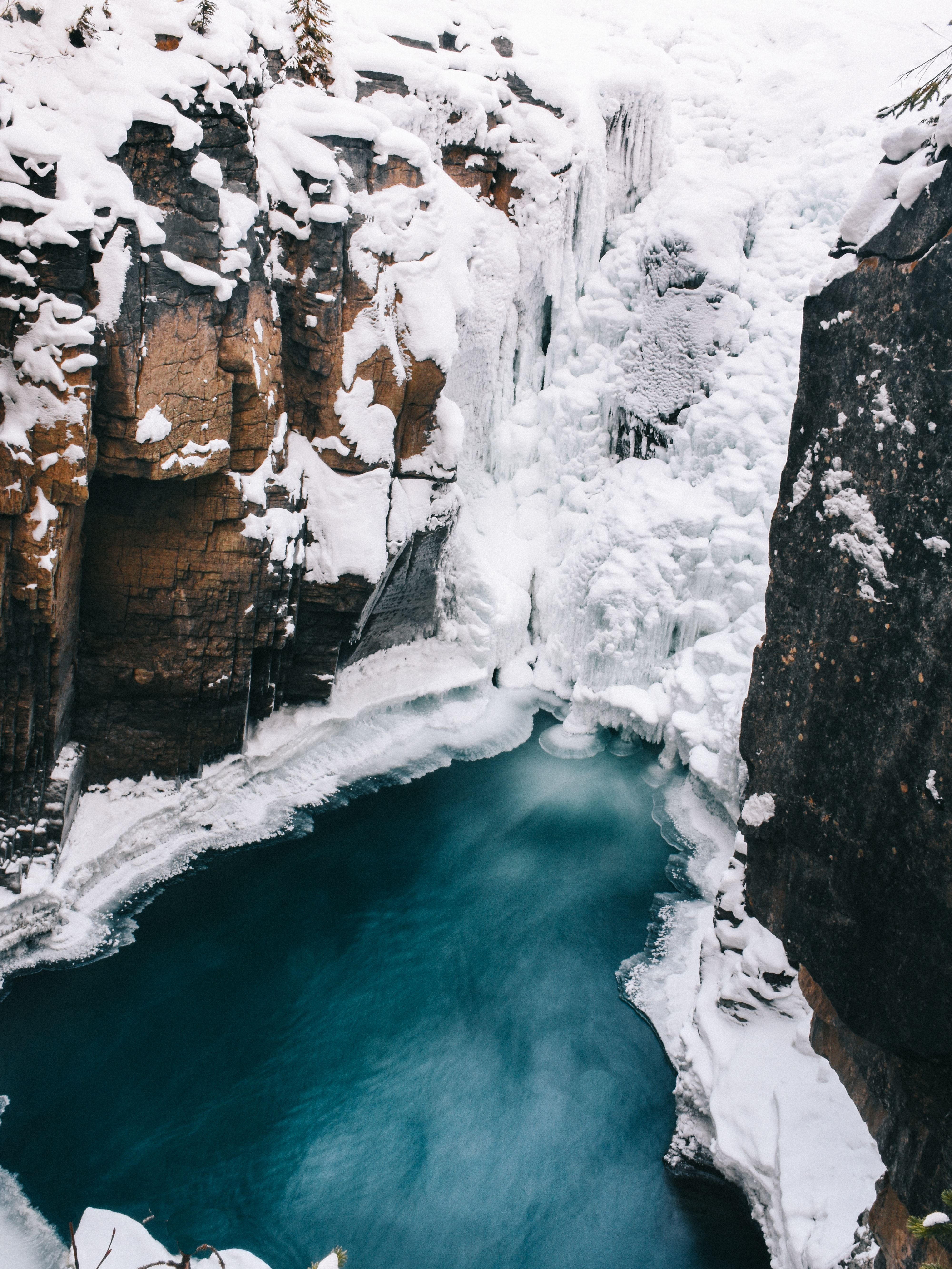 An icy mountain cliff is split by a frozen stream of water