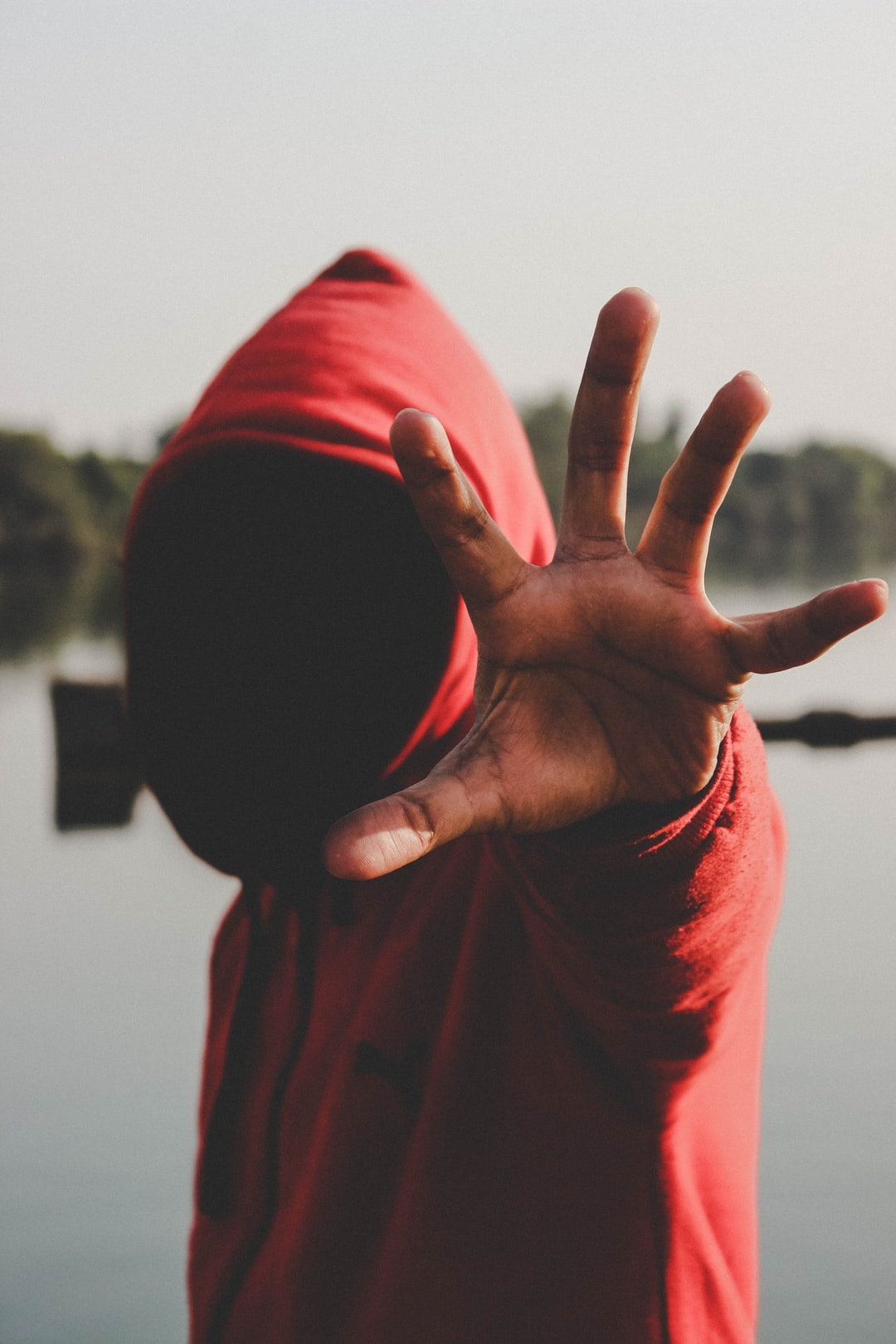 Man in hood stretching hand