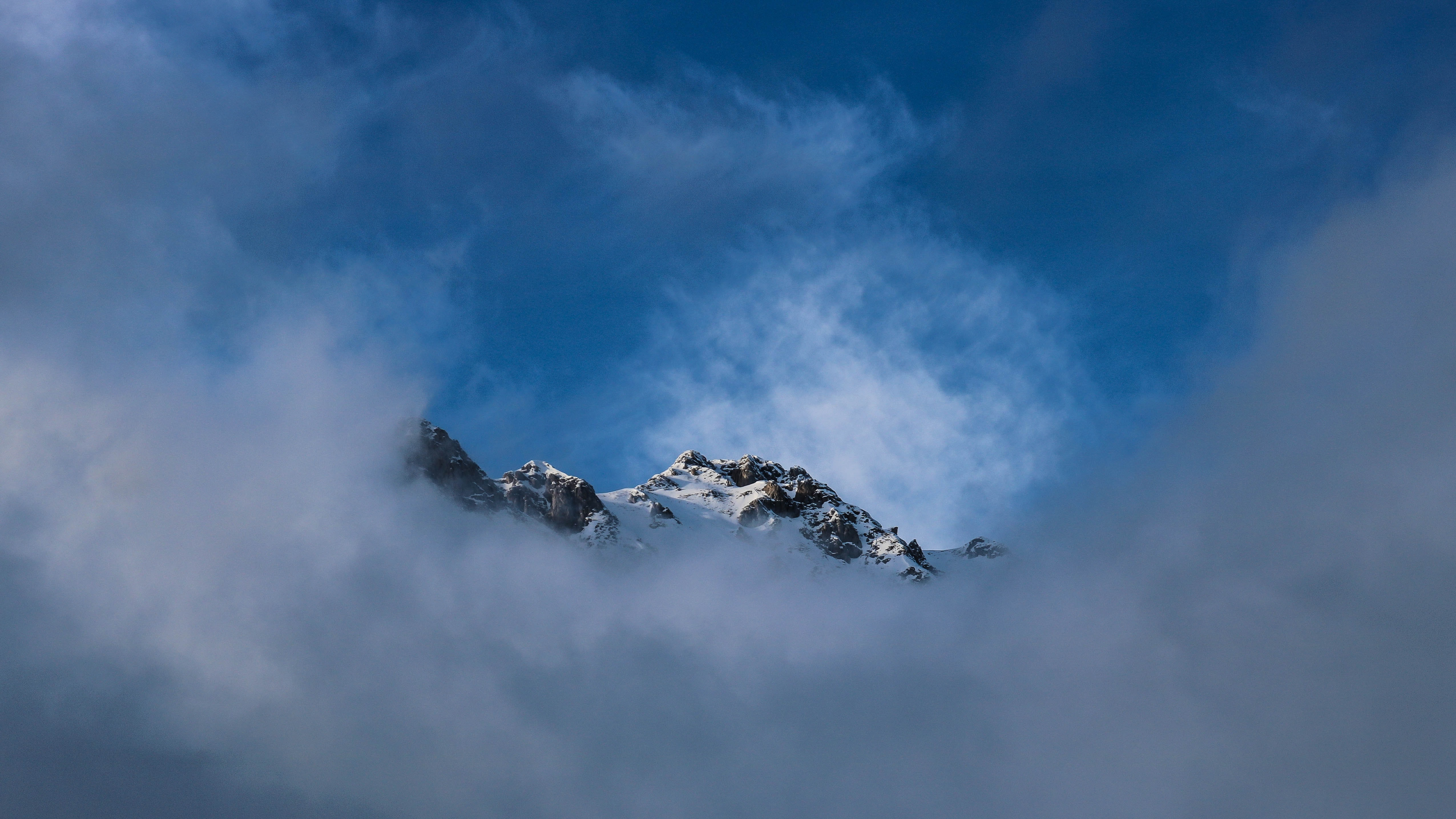 snow top mountain covered with fog during daytime