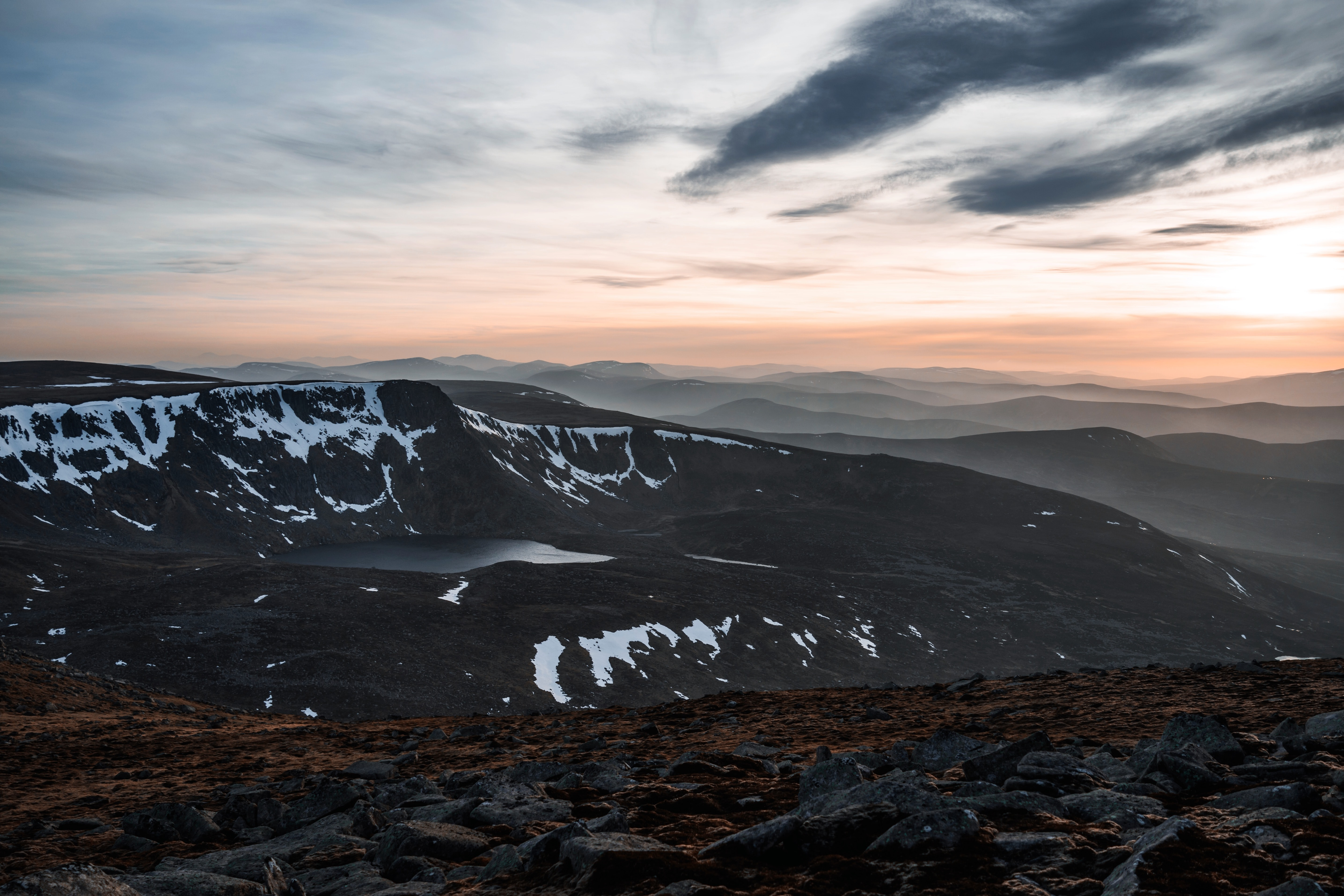 Clouds swept across sky with sunset  and snowy mountains in distance at Lochnagar