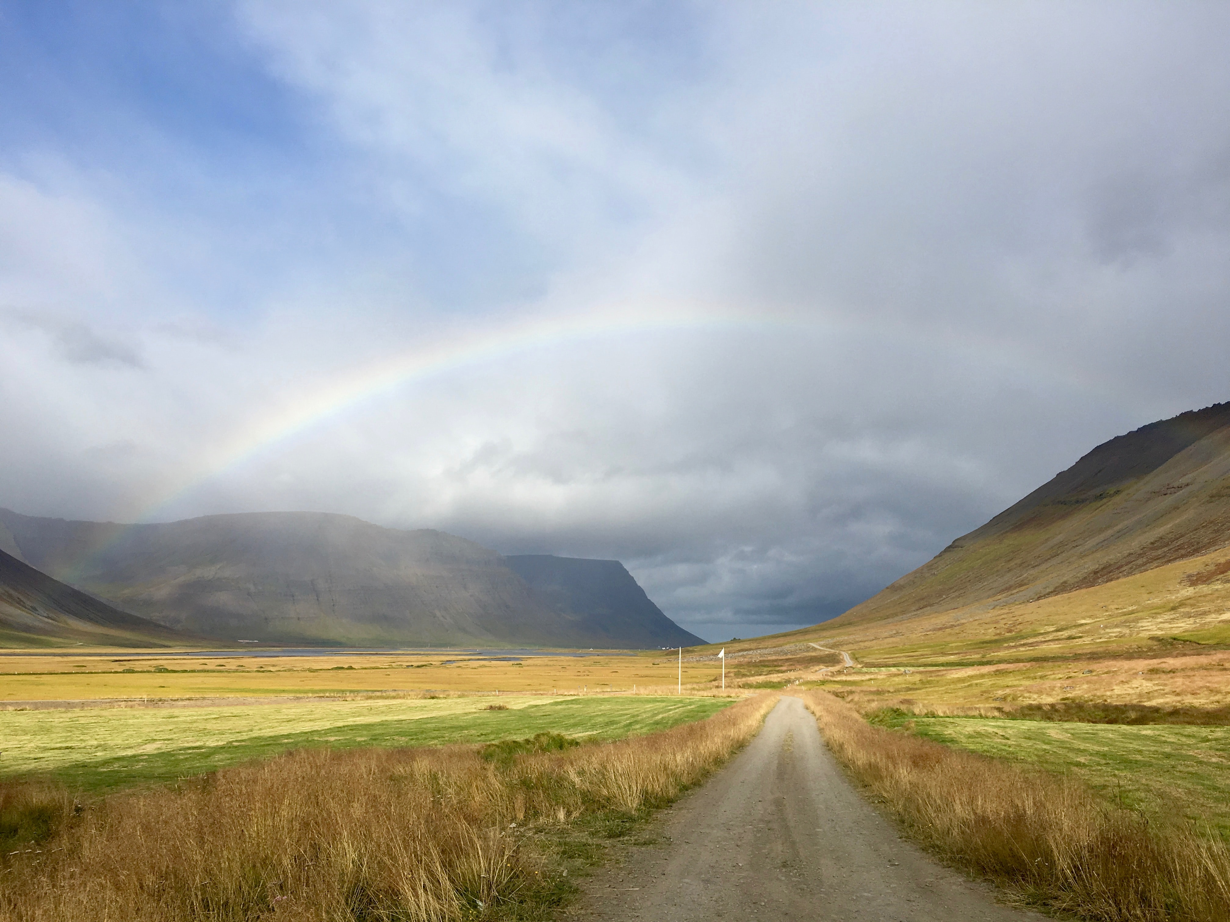 dirt path between brown and green field leading to a rainbow under blue and white cloudy sky