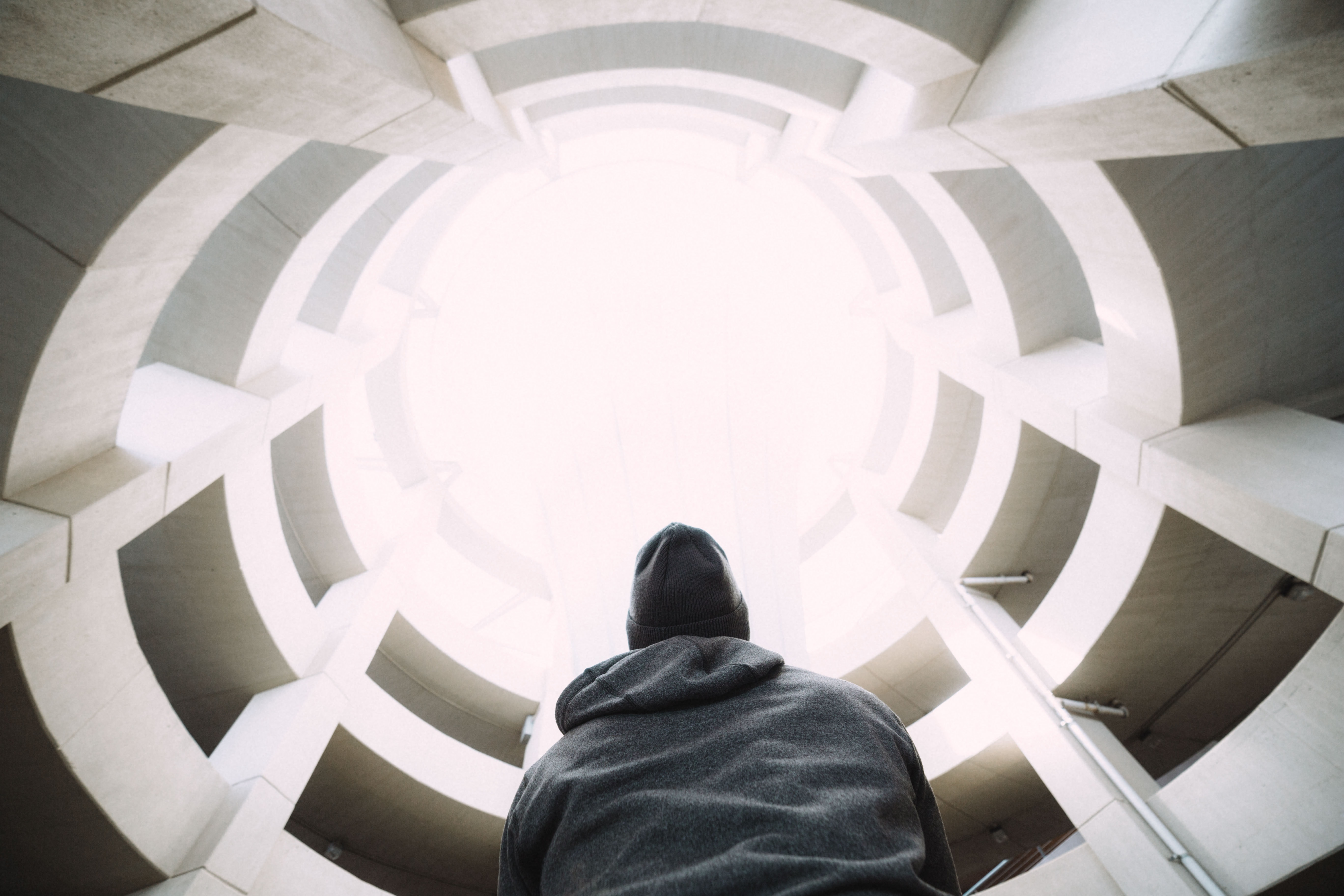 A person in a hoodie and a beanie looking up at the bottom of a concrete well