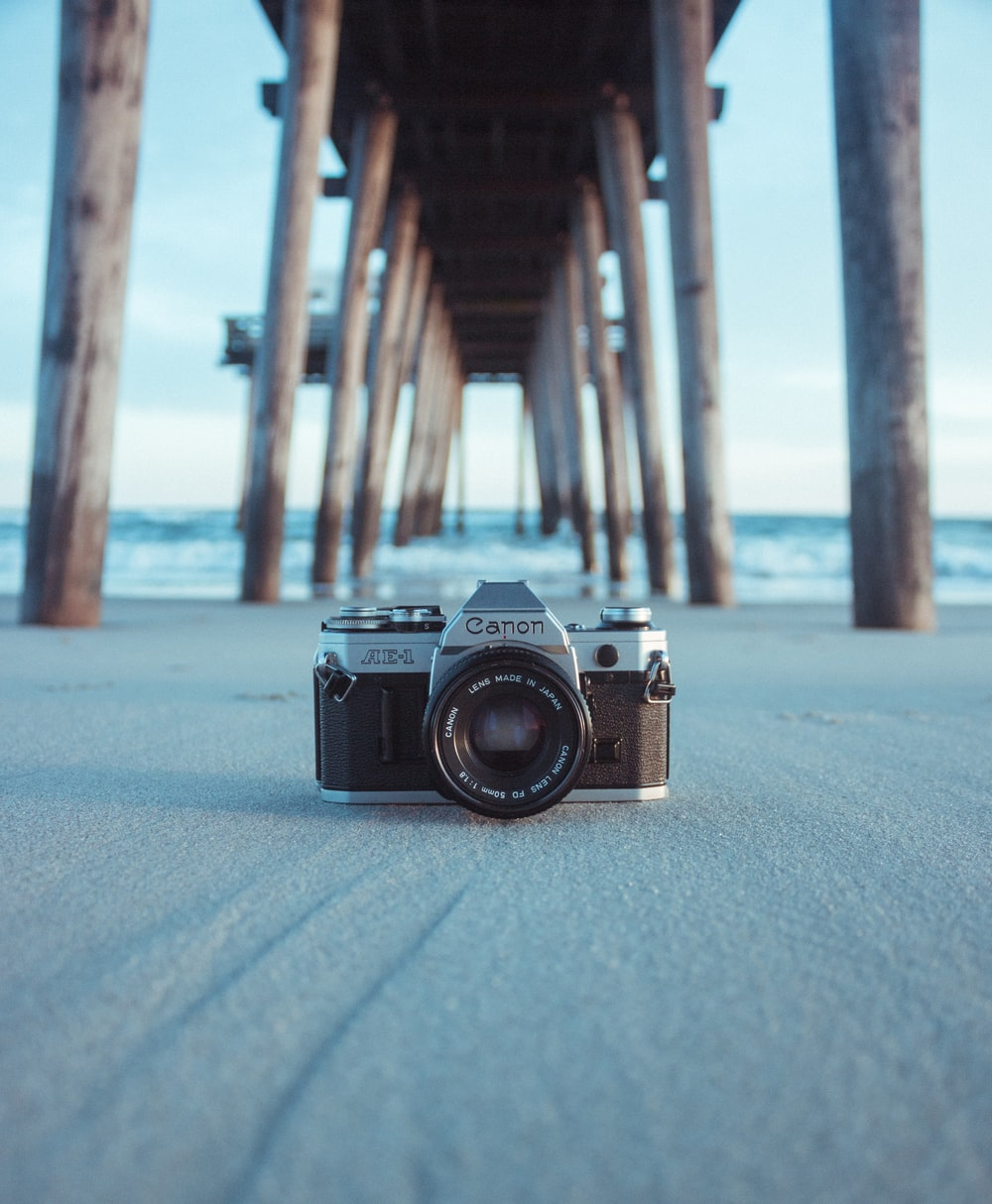 black and gray Canon AE-1 camera on gray sand under brown dock near body of water at daytime