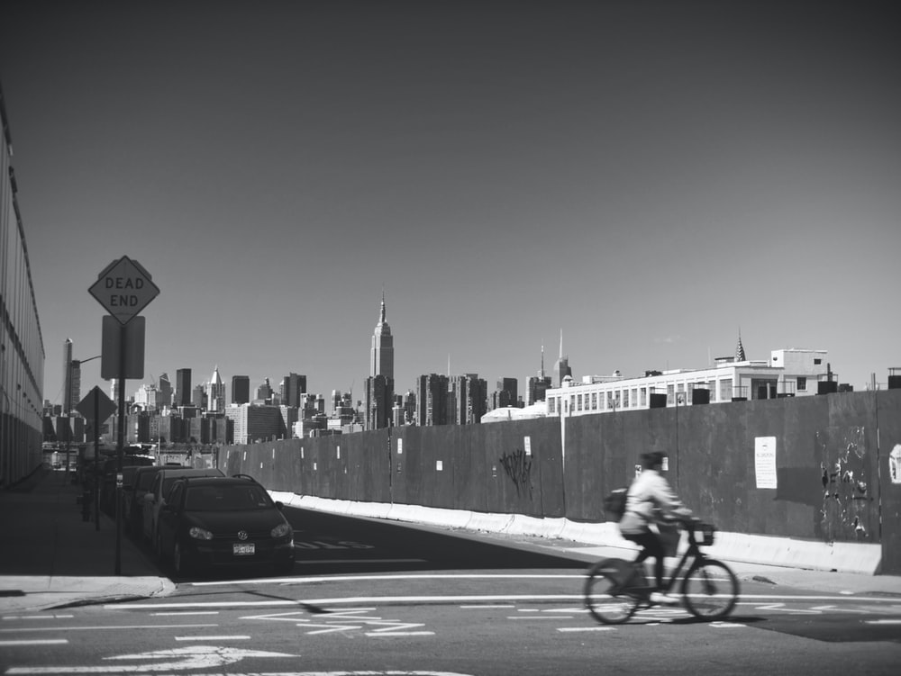 grayscale photo of person riding bicycle on road