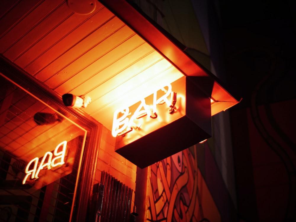 orange Bar signage beside bullet security camera