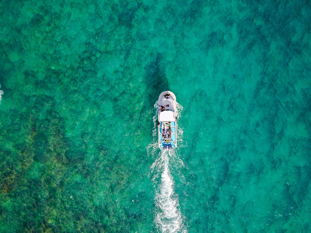 aerial photo of white boat sailing on body of water at daytime