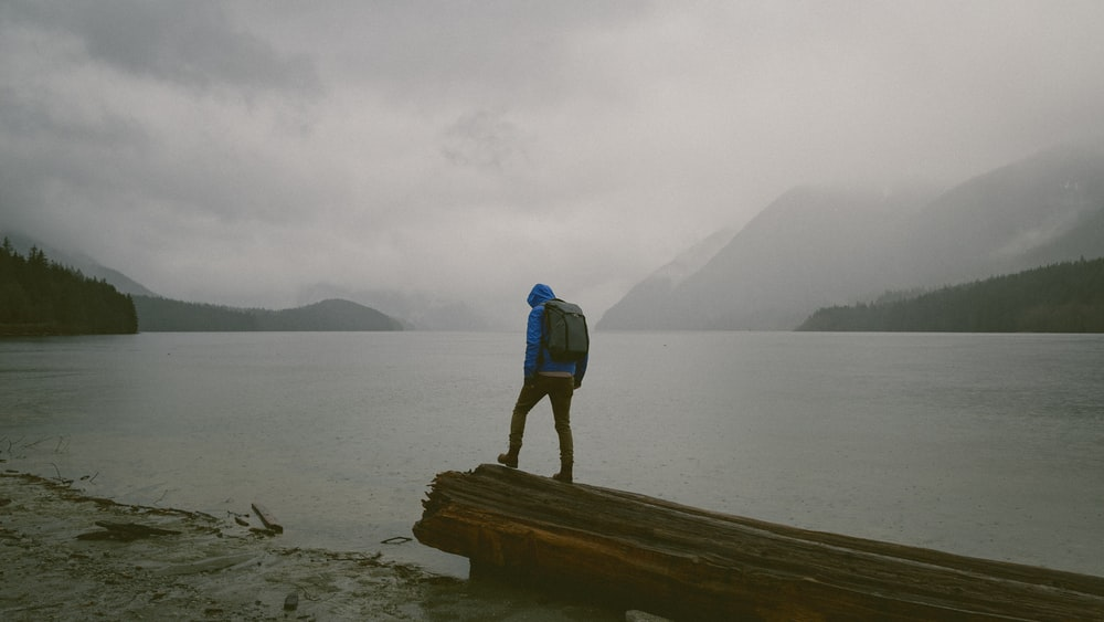 man standing on wooden platform in front of water during daytime