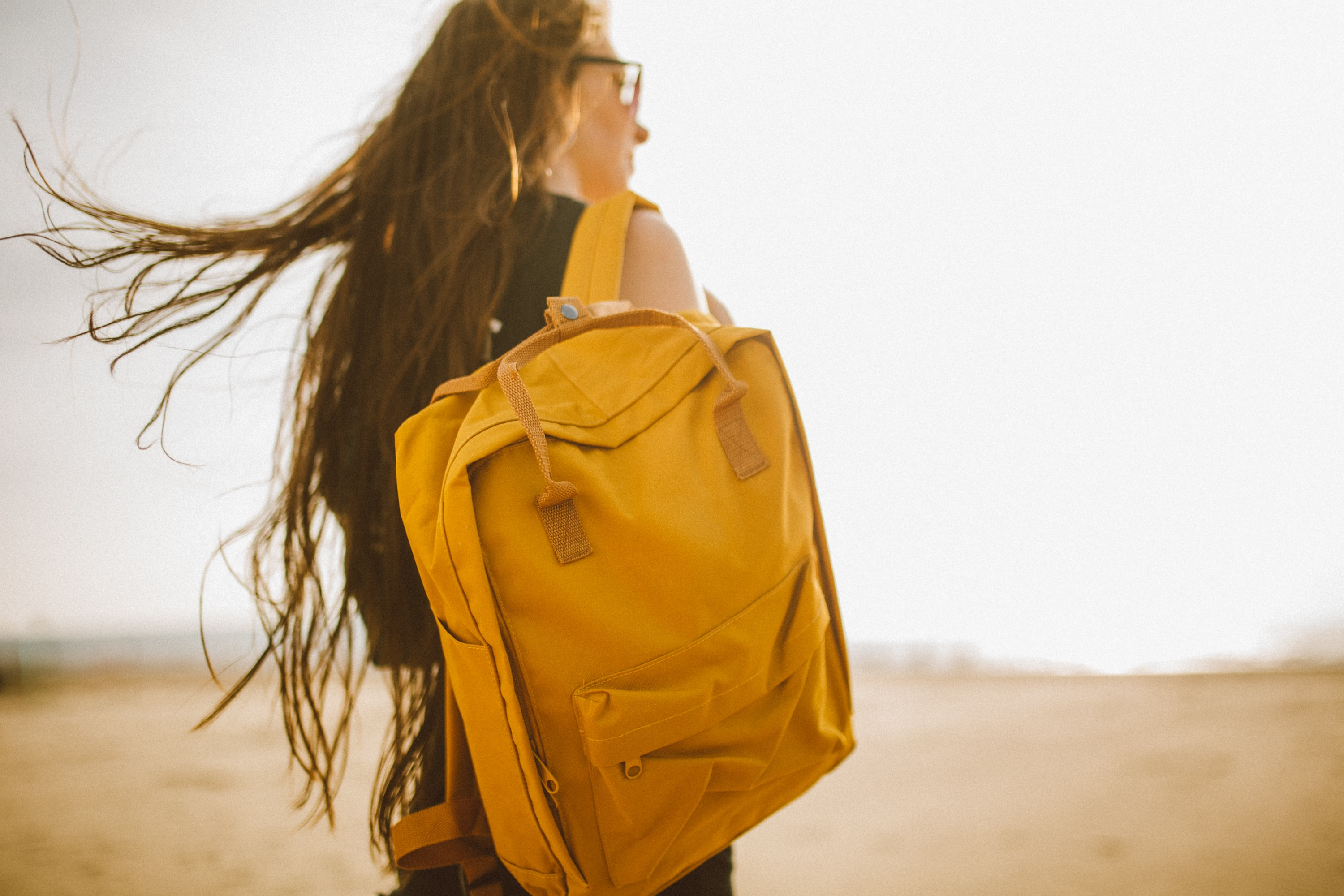 A woman carrying a yellow backpack on her back in Weston-super-Mare