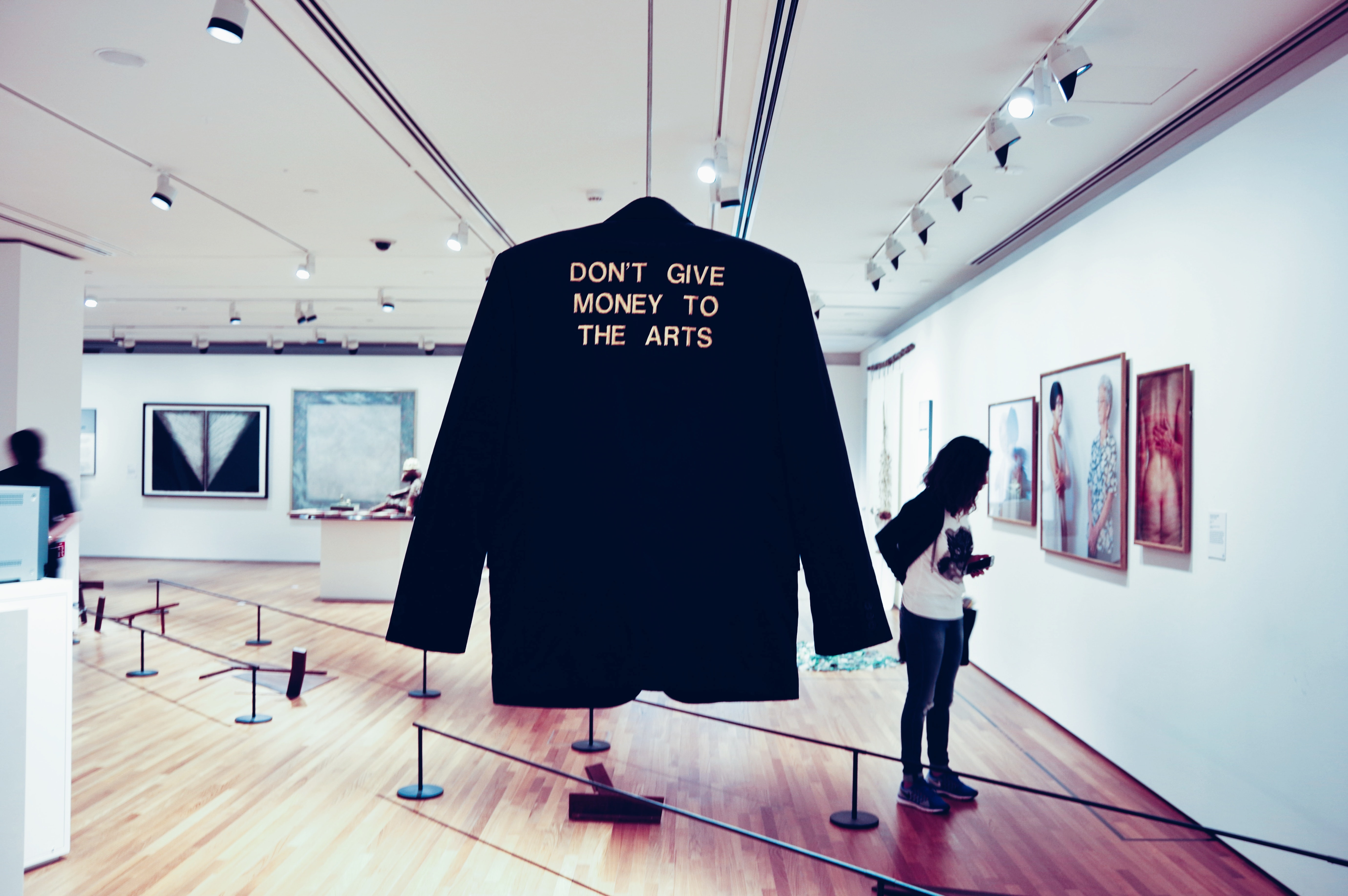 Gold text slogan on blazer hanging in art gallery with woman viewing art, National Gallery Singapore