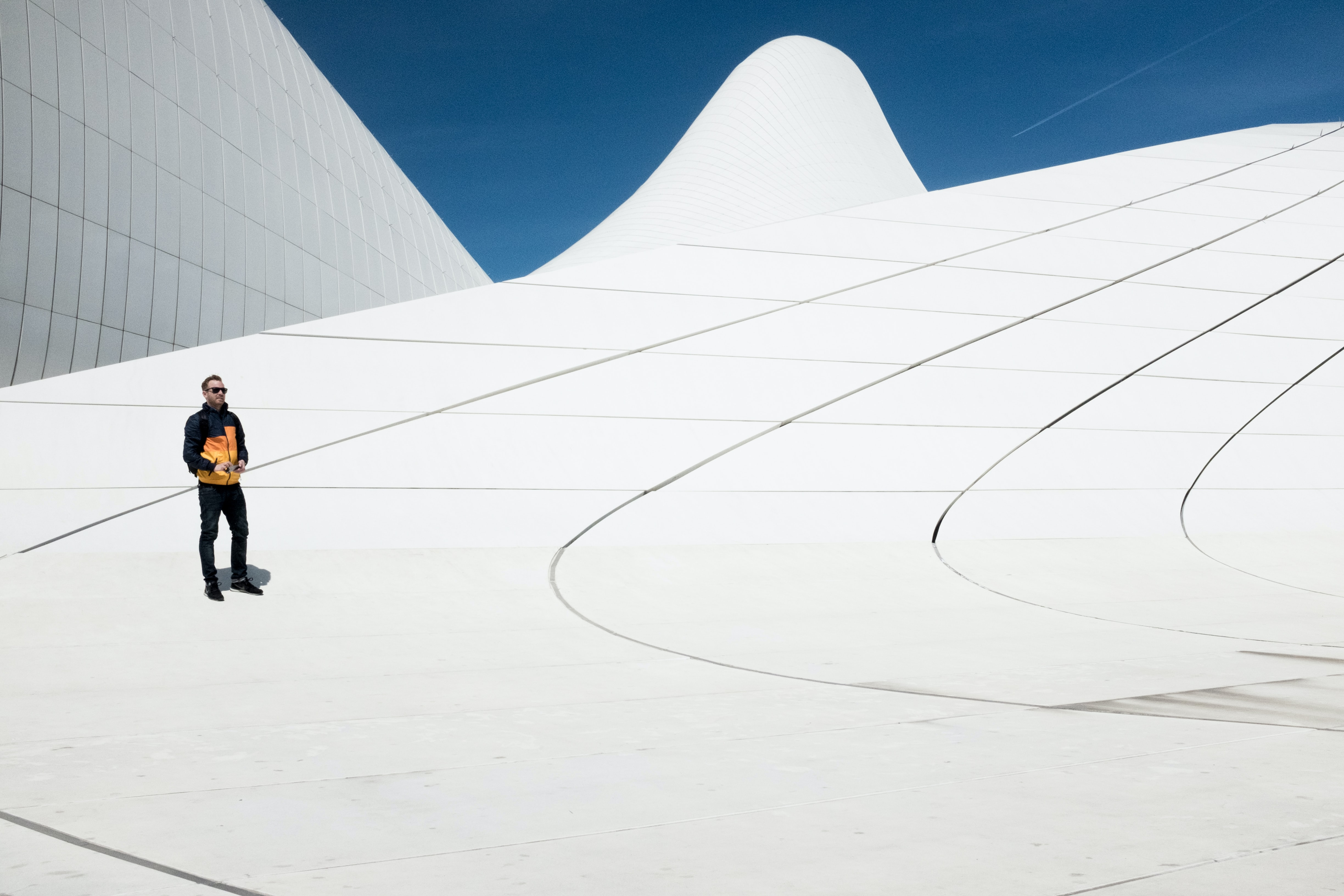 A man wearing a yellow and black jacket standing on an installation at Heydar Aliyev Centre
