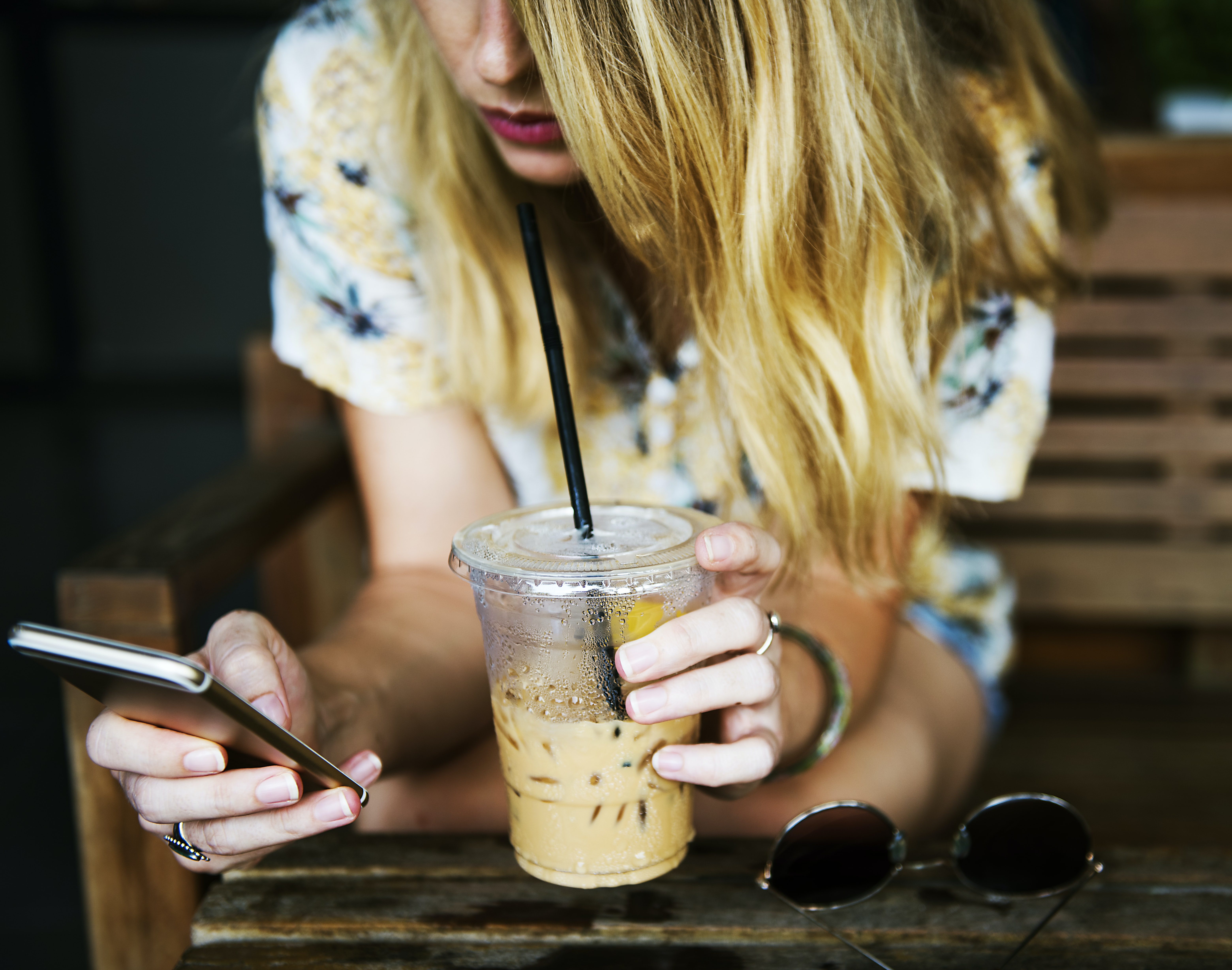 A blonde woman drinking iced coffee while using an iPhone