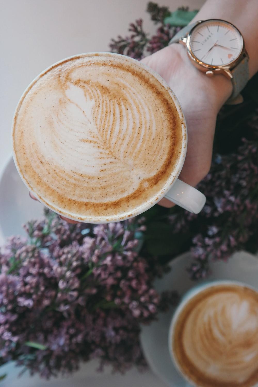 person holding white ceramic espresso cup