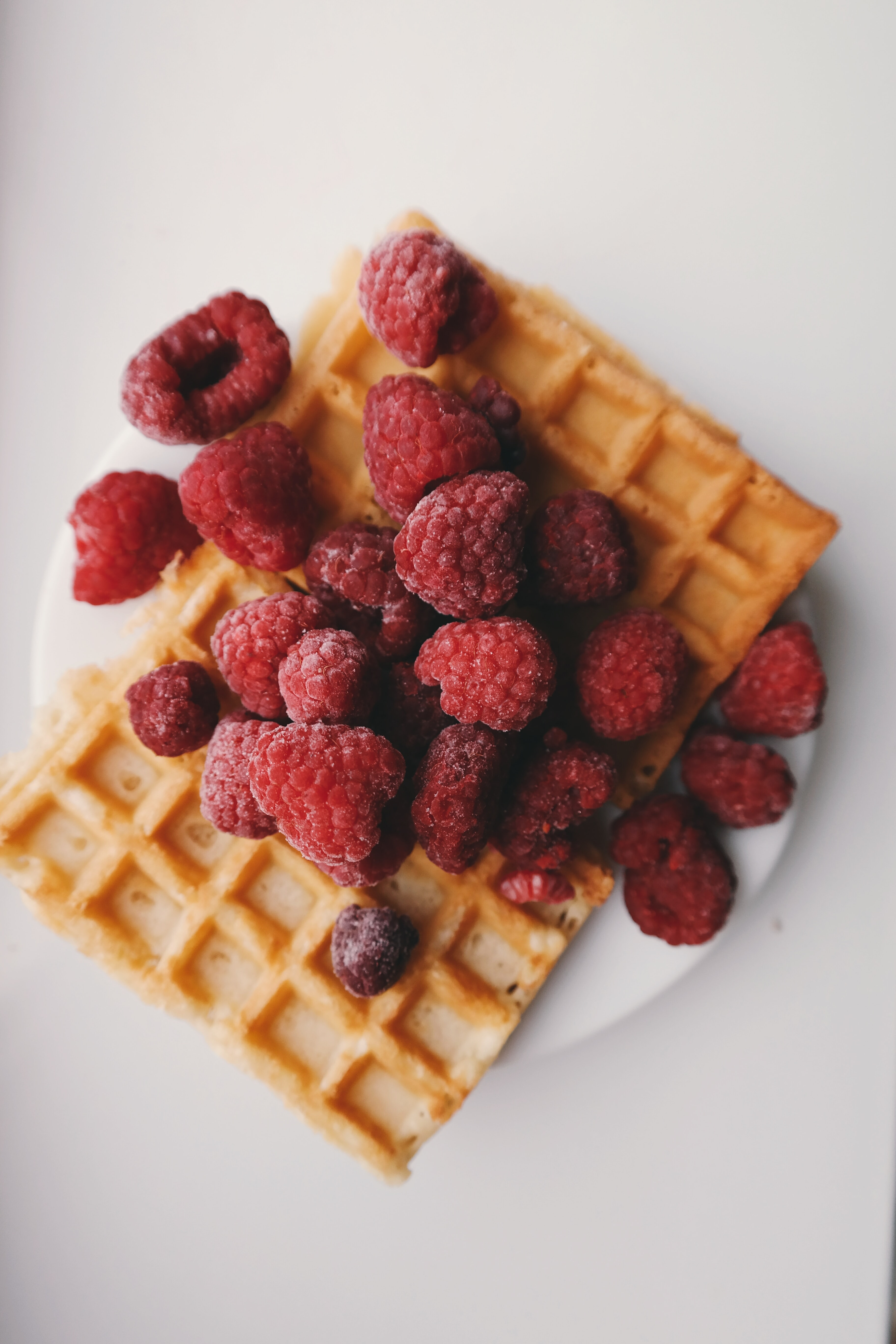 Raspberries on top of a rectangle shaped waffle.