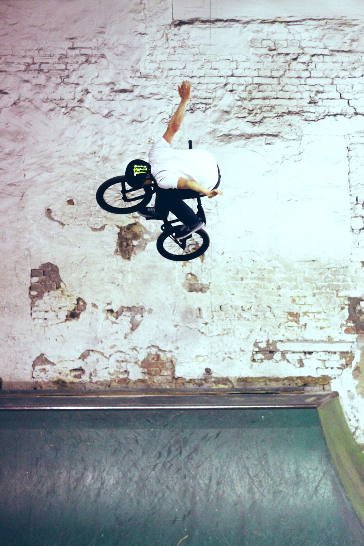 man riding black BMX bike doing bike tricks
