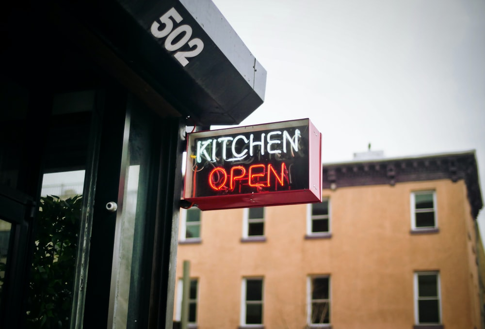 white and red neon lighted kitchen open signage during daytime