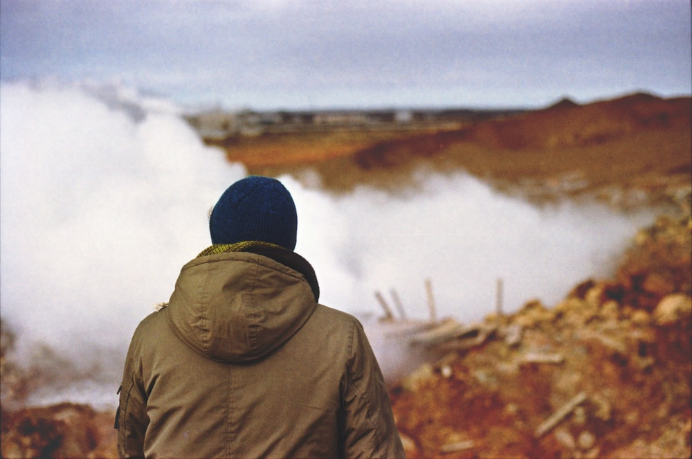 person in brown hooded jacket standing near fog