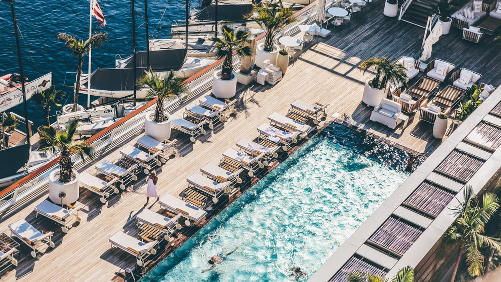 worm's eye photography of swimming pool with sun lounge chairs nearby blue sea