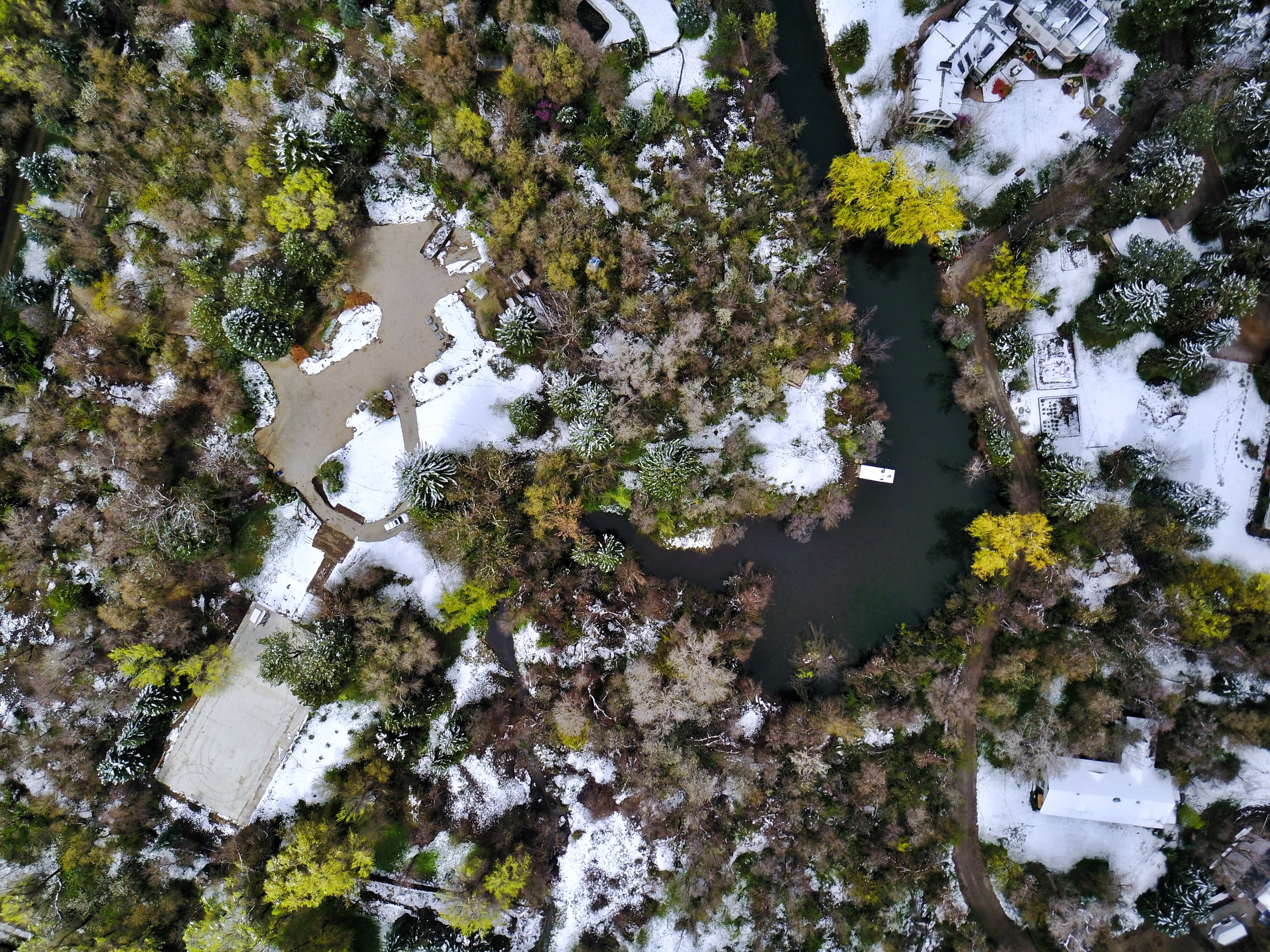 A drone shot of Salt Lake City, Utah showing trees, water, streets and snow