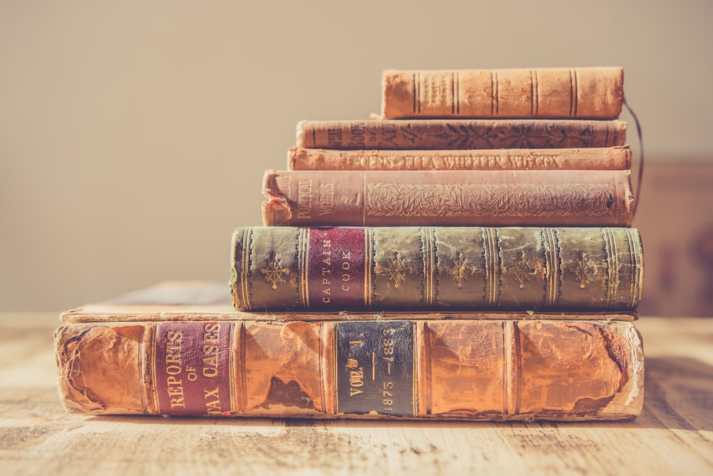 shallow focus photography of stack of books