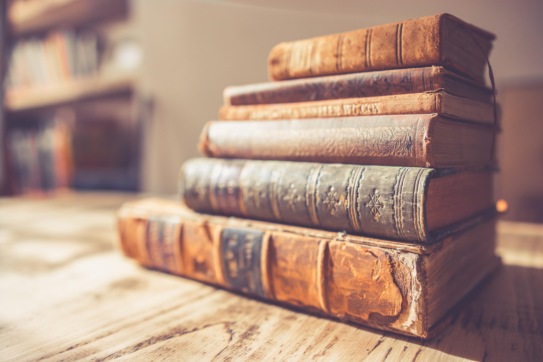 stack of six brown hardbound books