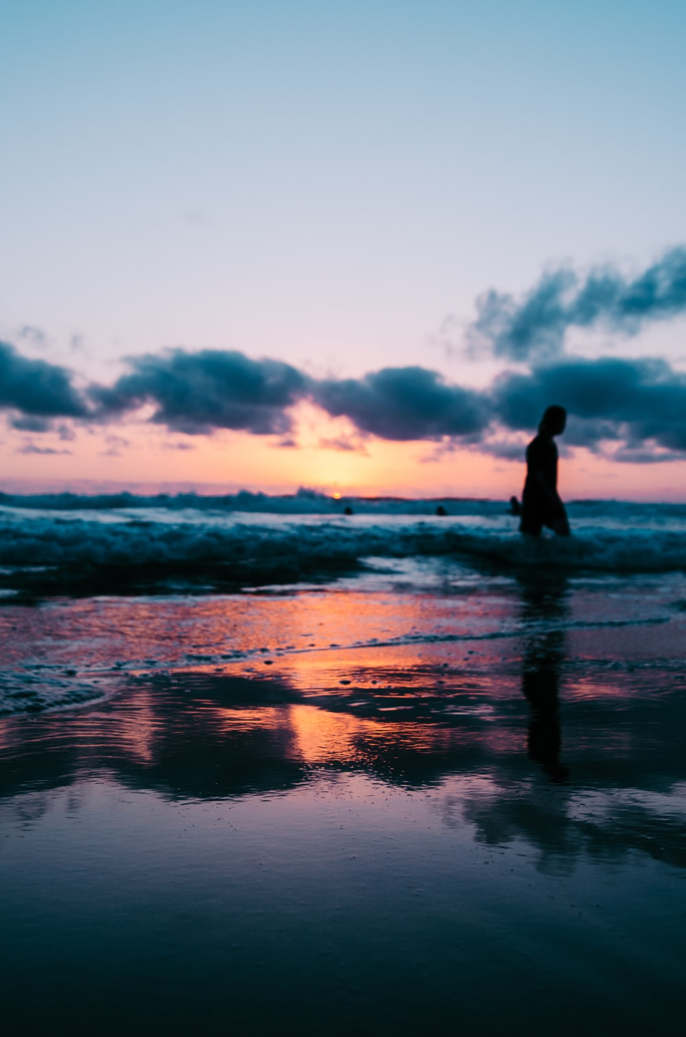 silhouette photo of a person walking on seashore under cloudy sky during golden hour