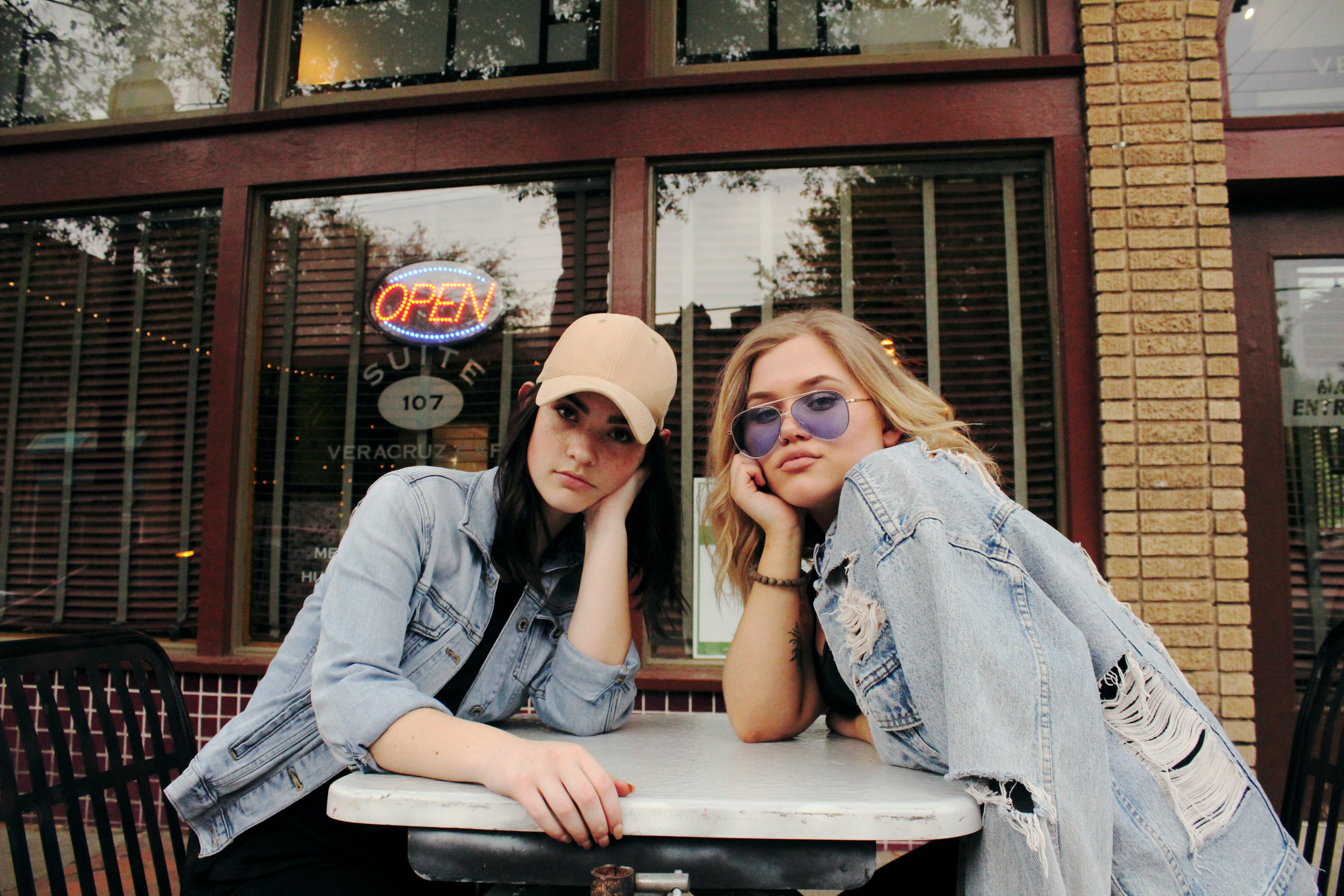 Two women in denim sit at a table in front of a business in Dallas
