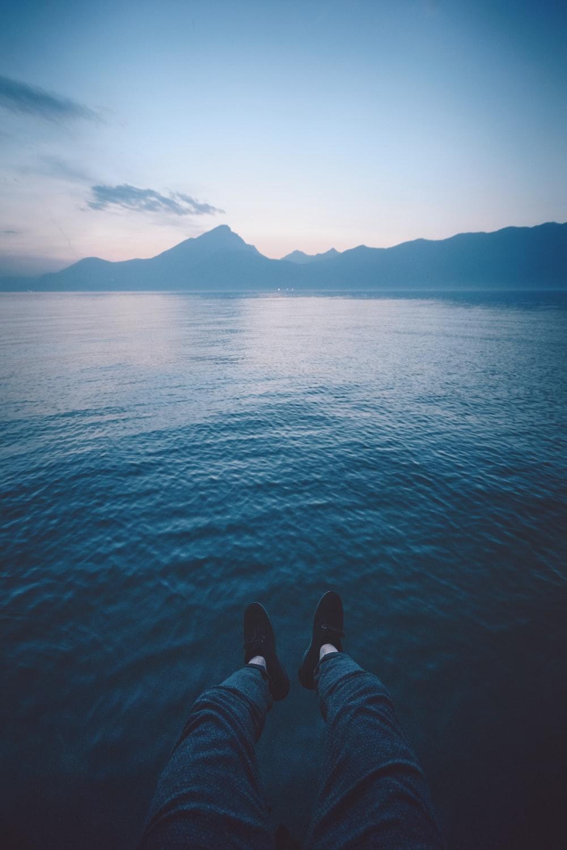 man sitting beside calm body of water