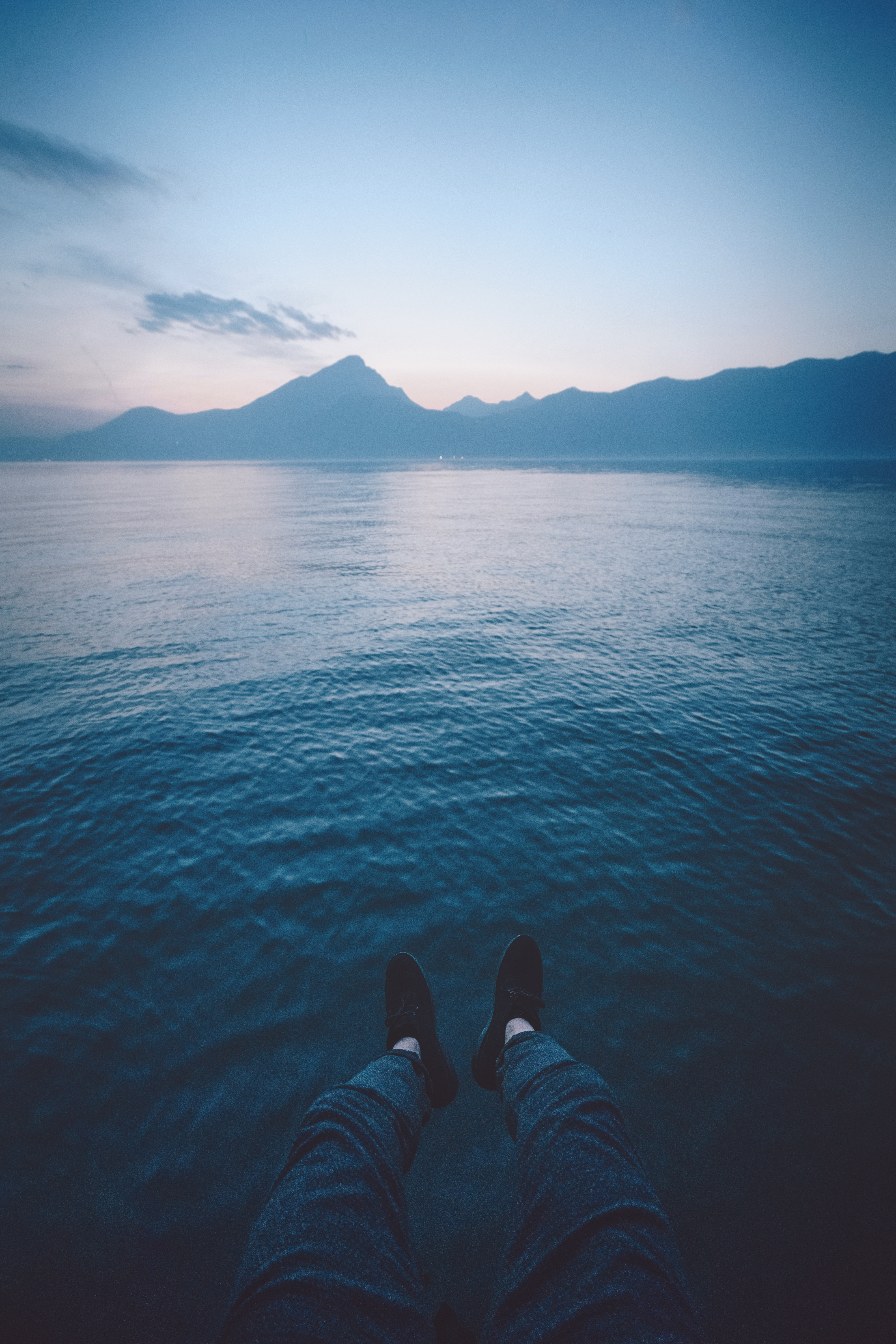 A person's feet hanging over water while overlooking the mountains in Pai at sunset