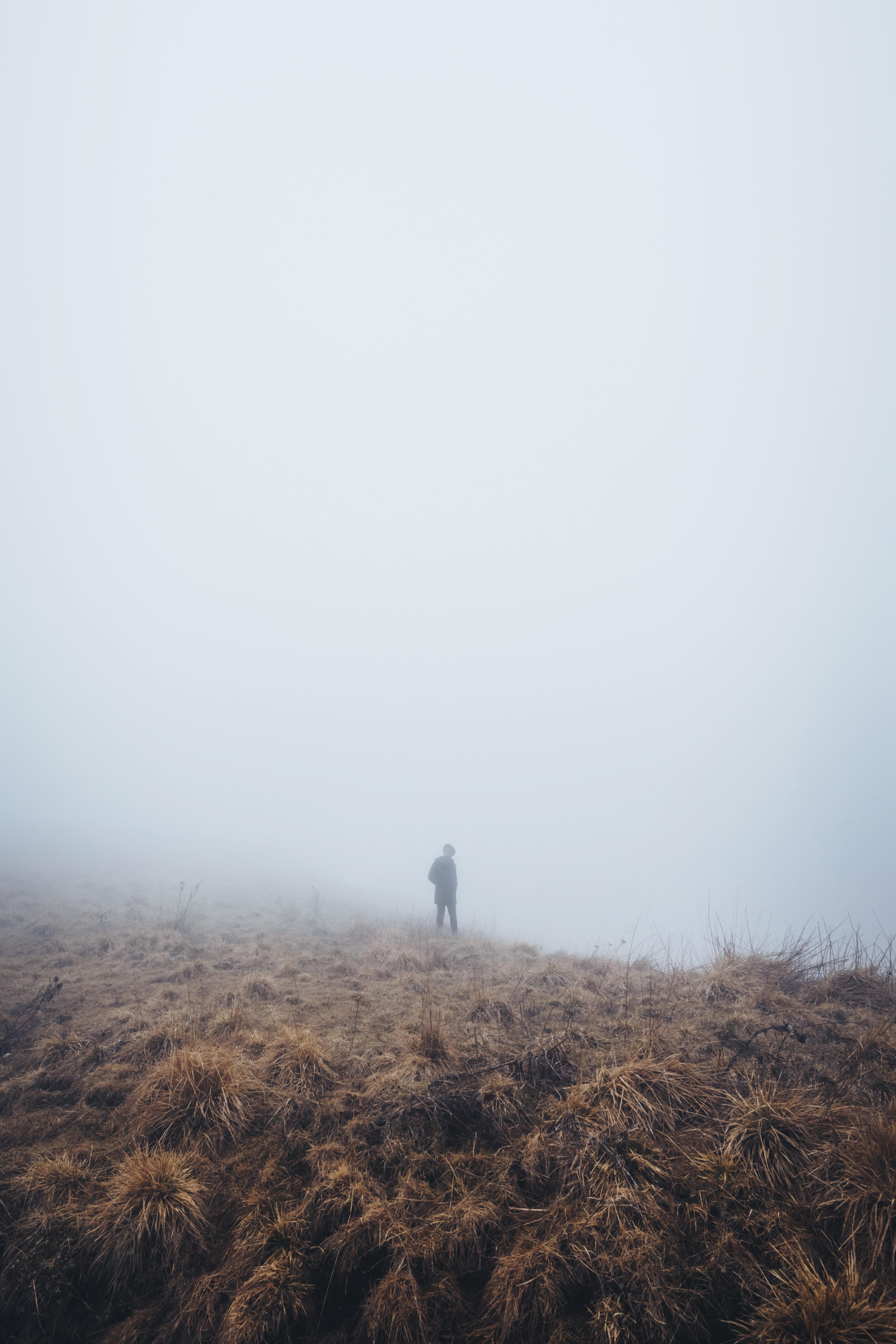 Silhouette of hiker walking through desolate prairies on a foggy day