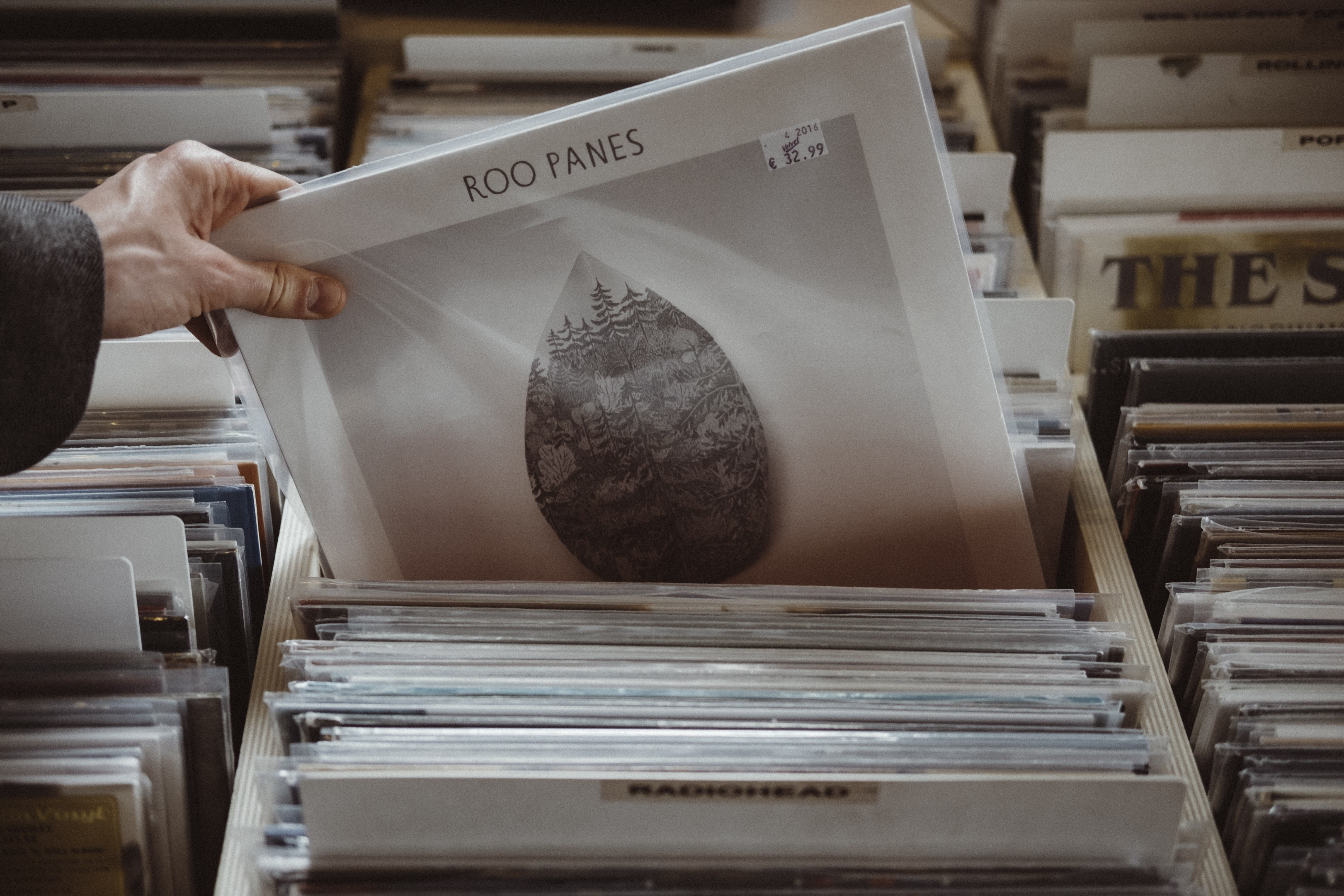 A person picking out a Roo Panes vinyl record in a record store