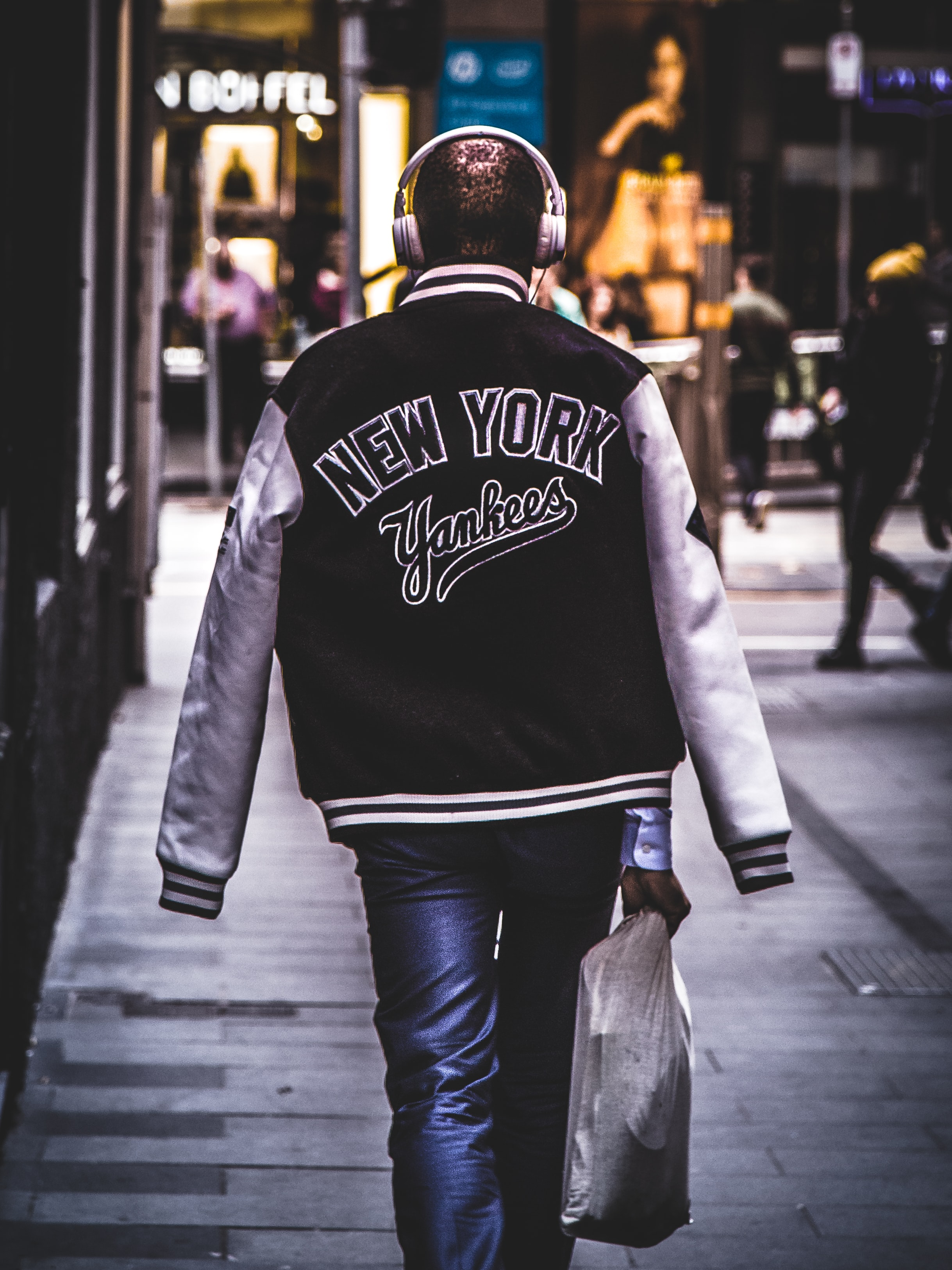 The back of a man wearing a new york Yankee's jacket with headphones walking on the street