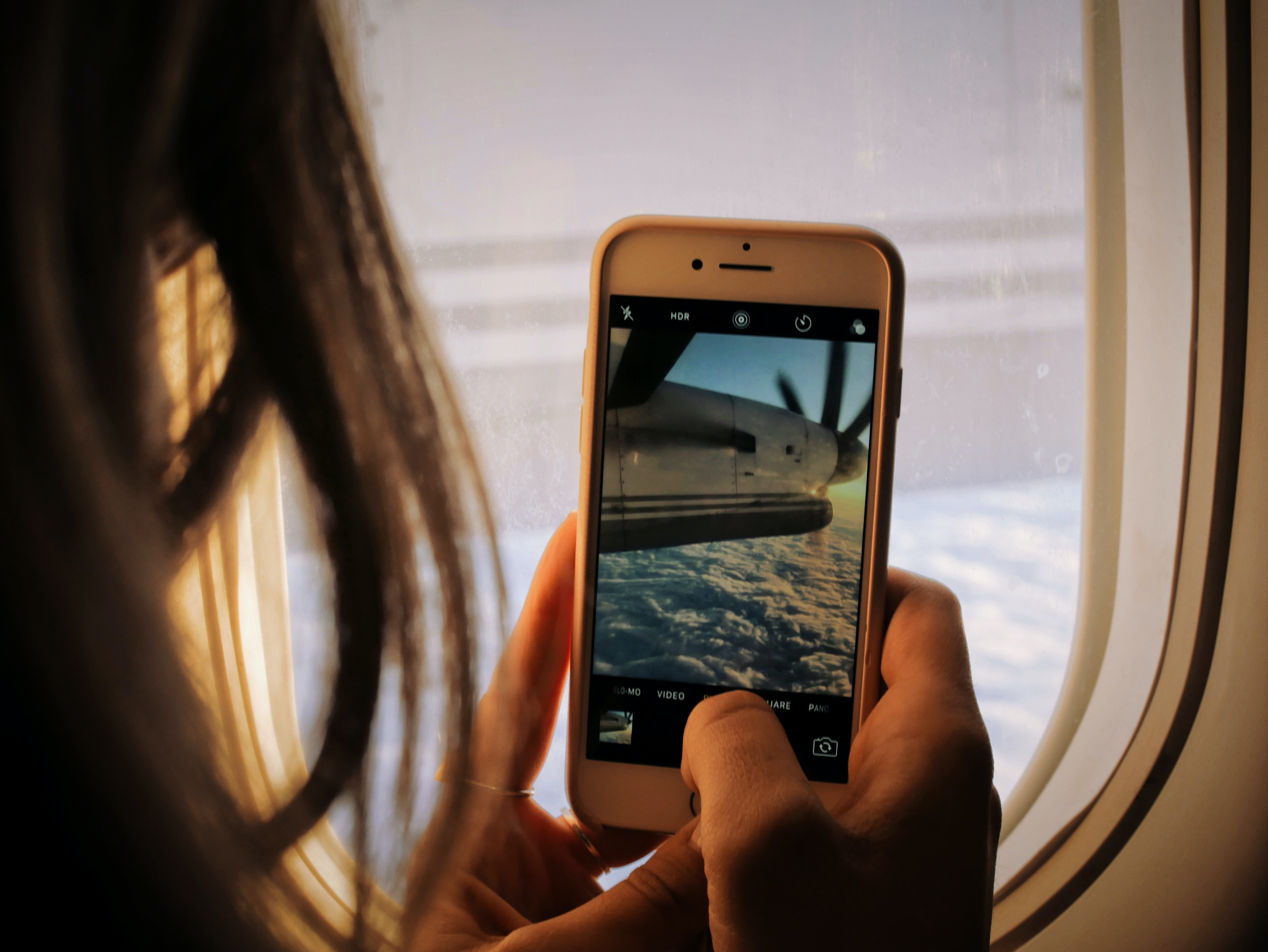 A person taking a picture of a plane wing and jet.