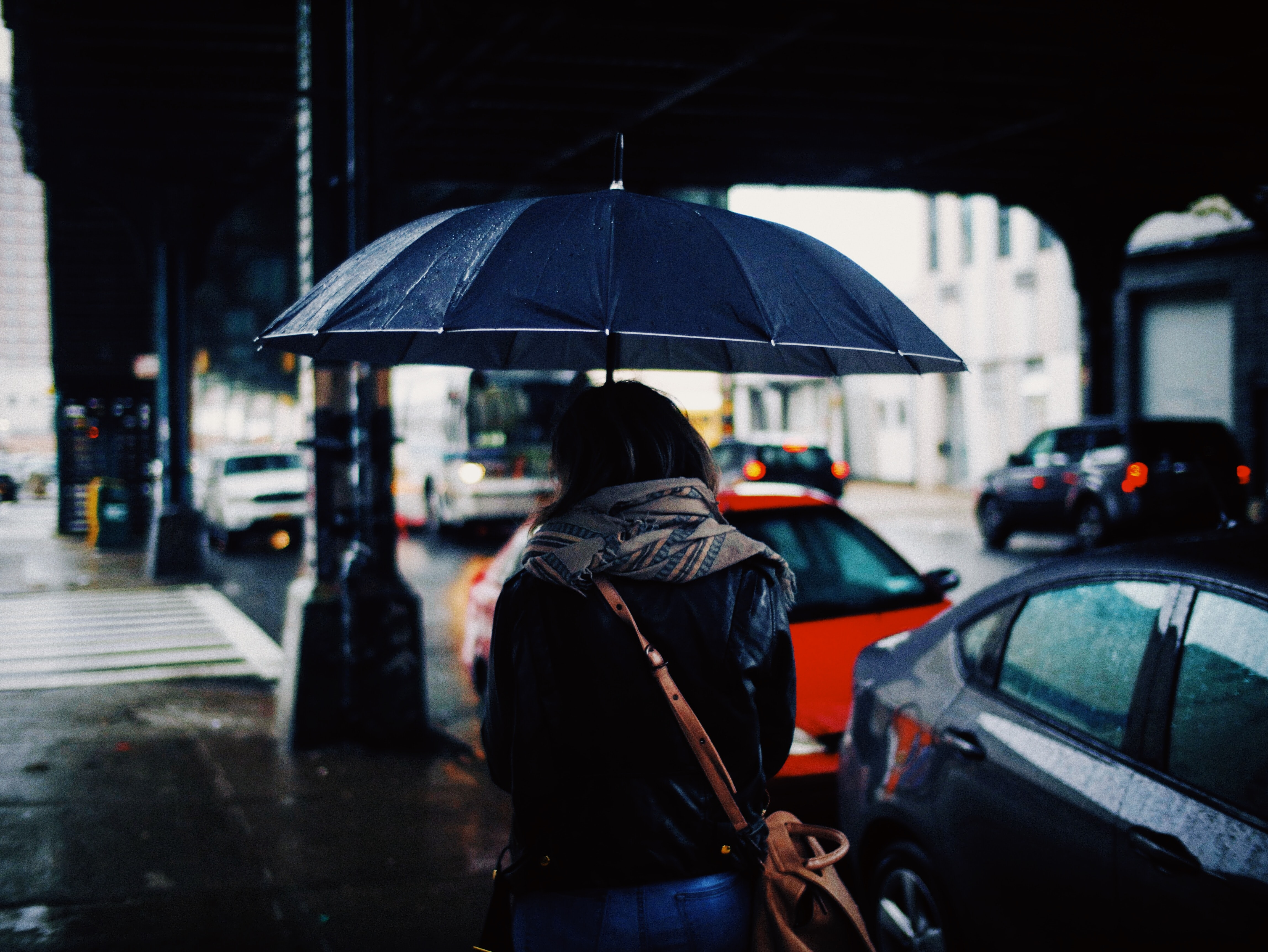 woman holding umbrella walking on street during daytime