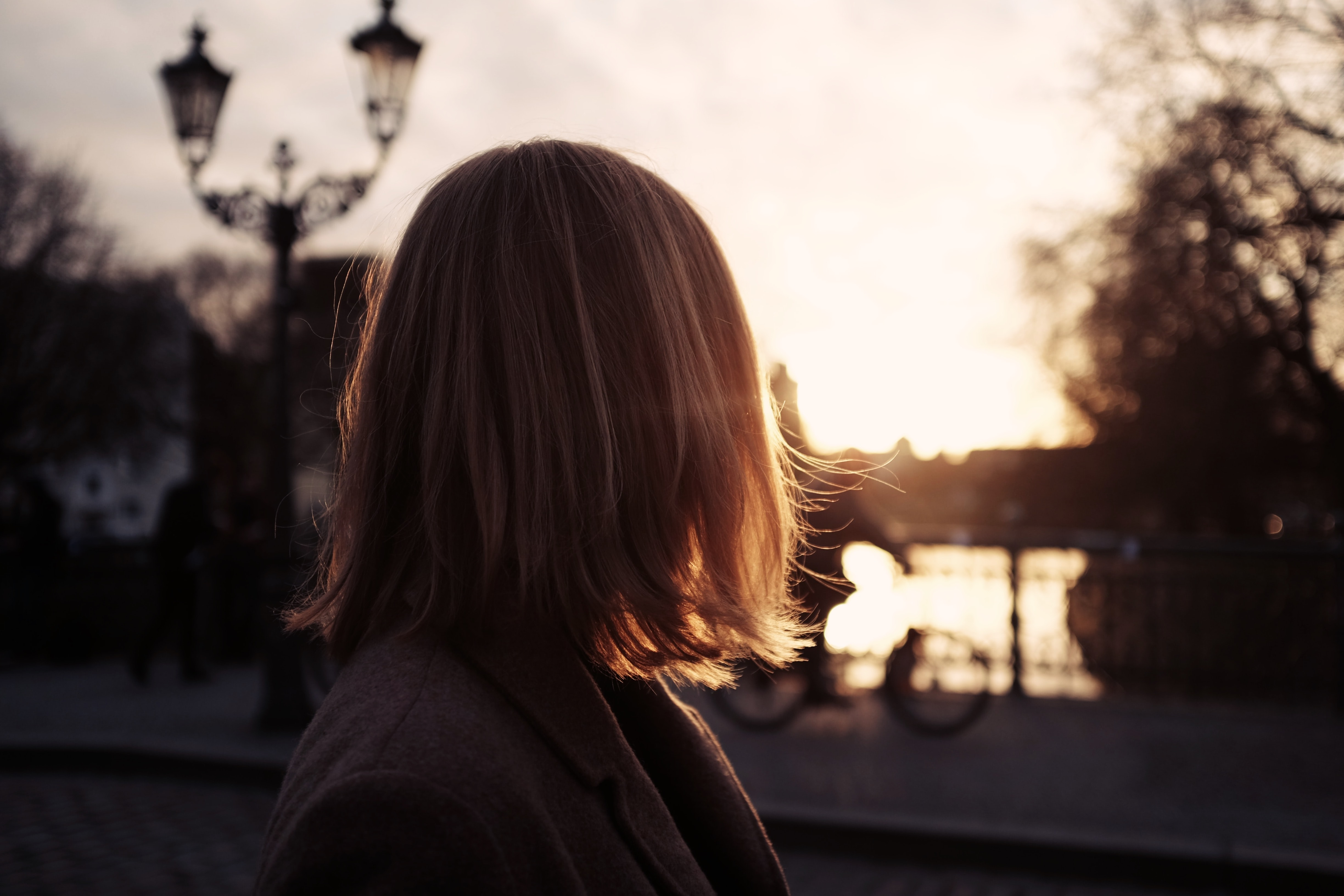 A woman with short blond hair looks away from the camera during sunset in Admiralsbrücke.