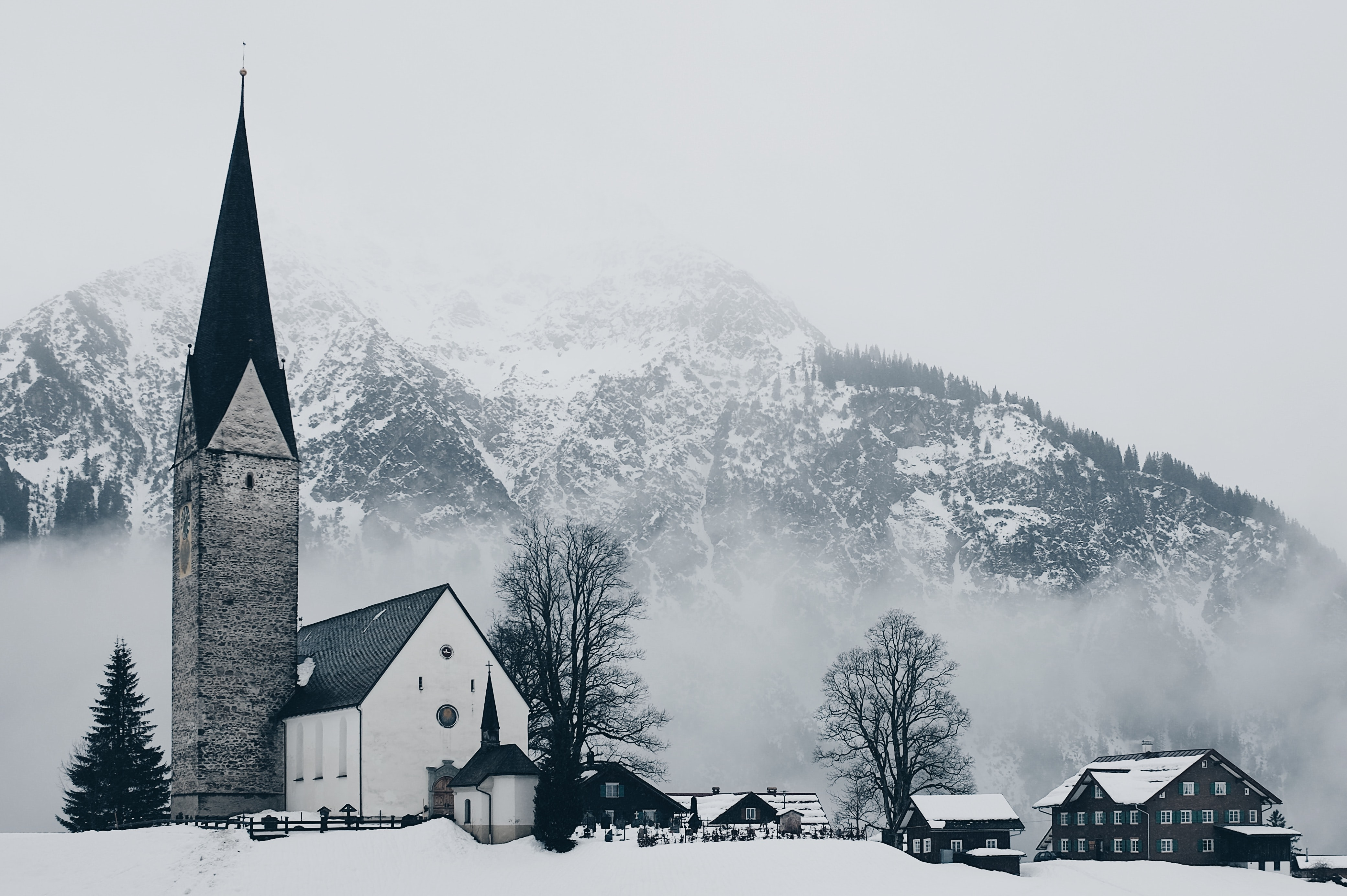A snowy village and a church with a mountain covered in a deep hanging cloud