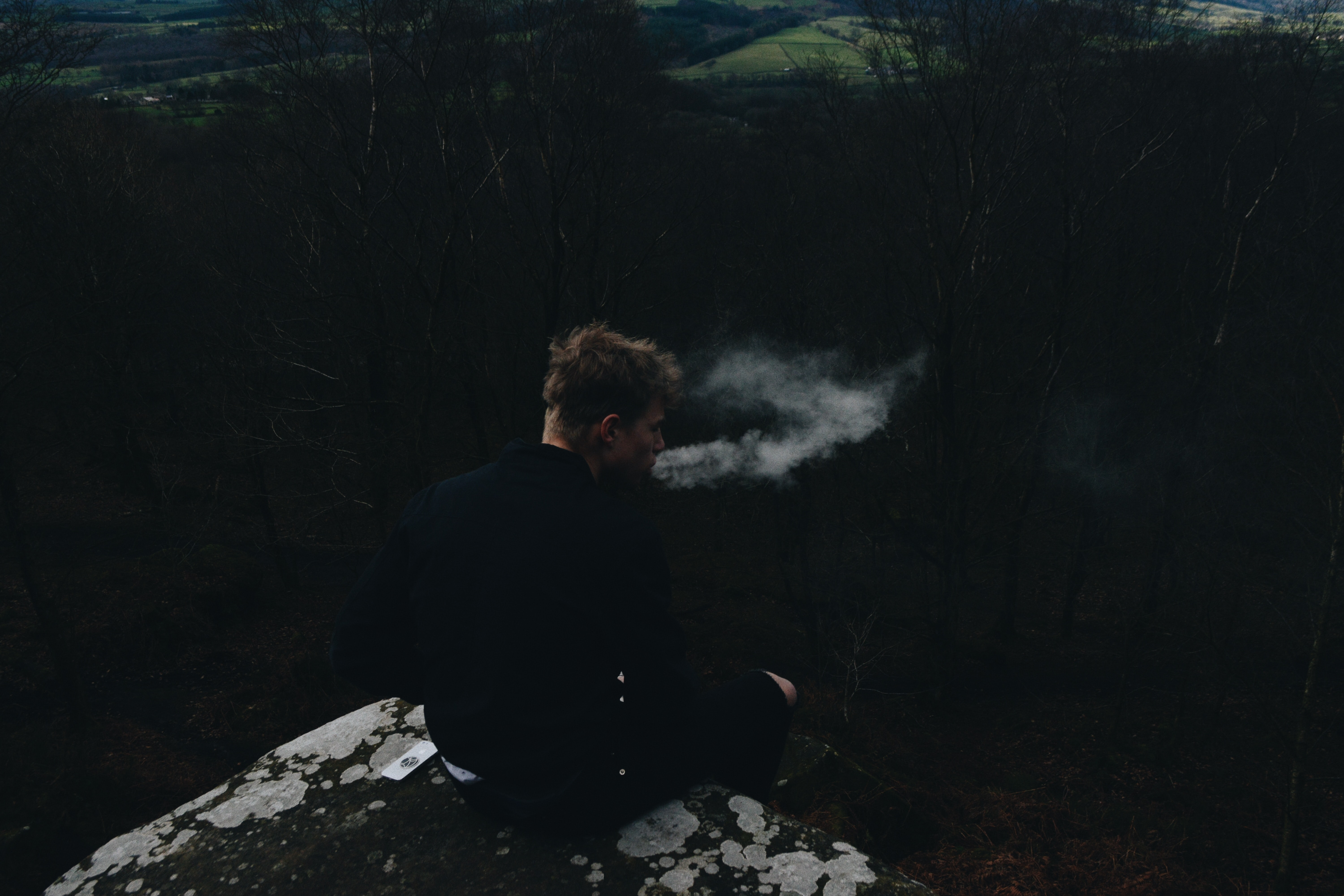 smoking man sitting on rock formation