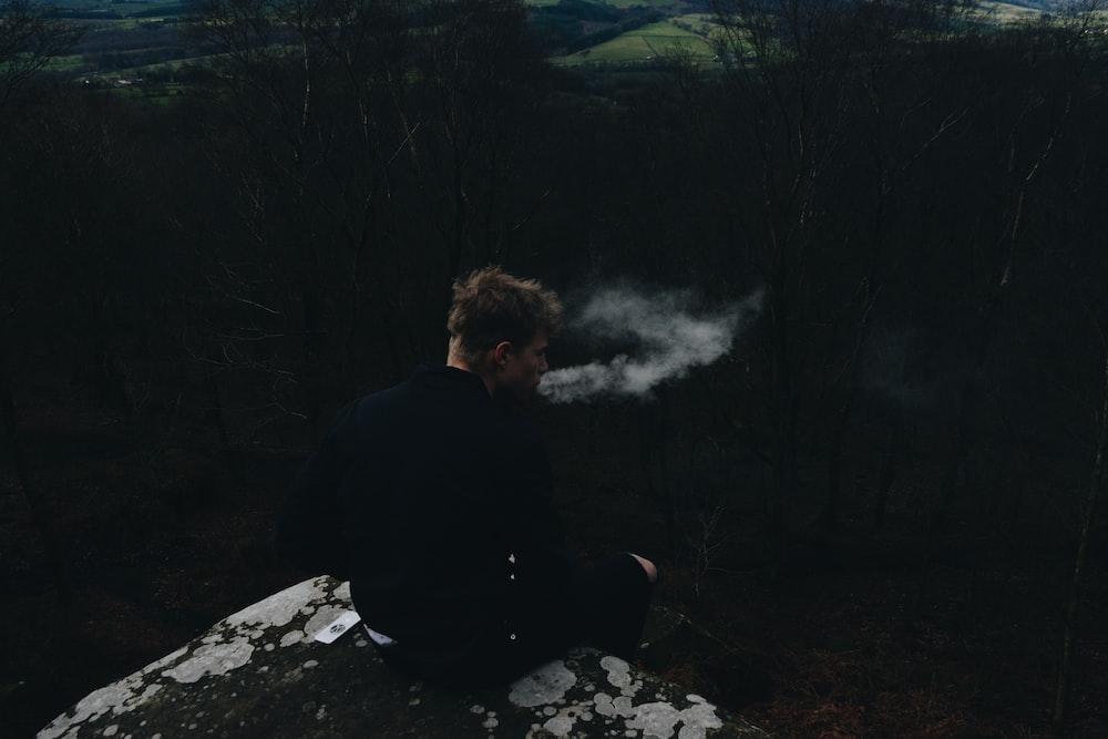 smoking man sitting on rock formation