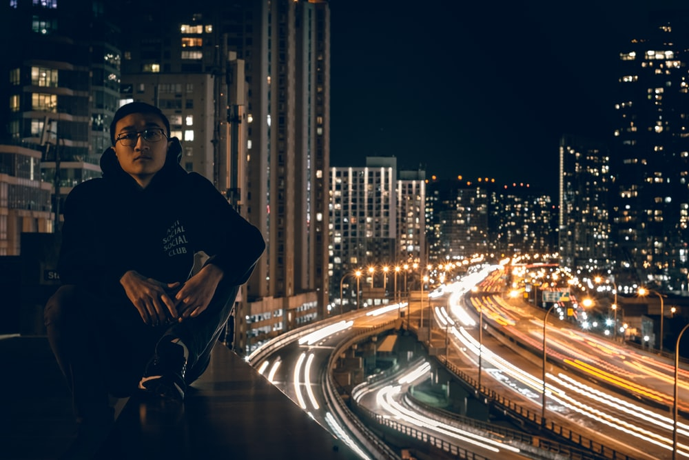 man sitting on rooftop during nighttime in timelapse photo