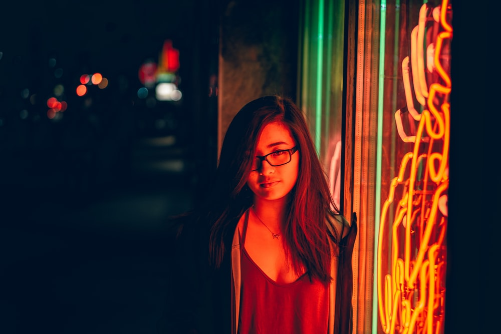 woman smirking beside glass window with turned on neon signage during night