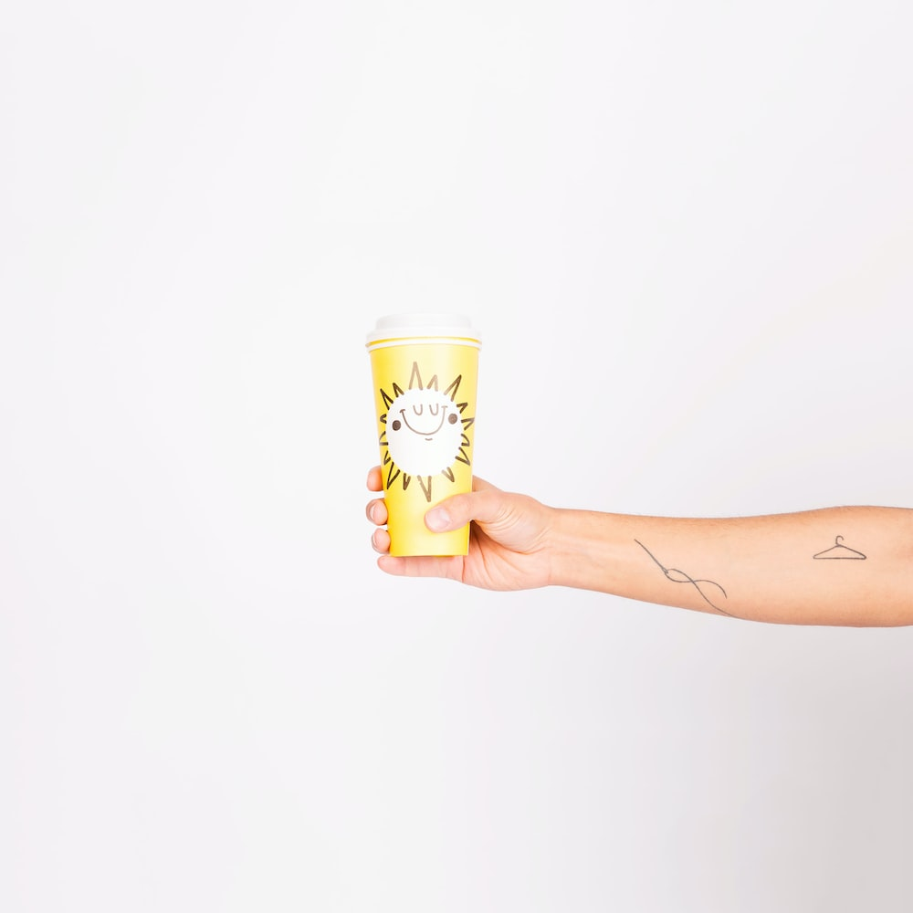 person holding yellow drinking cup