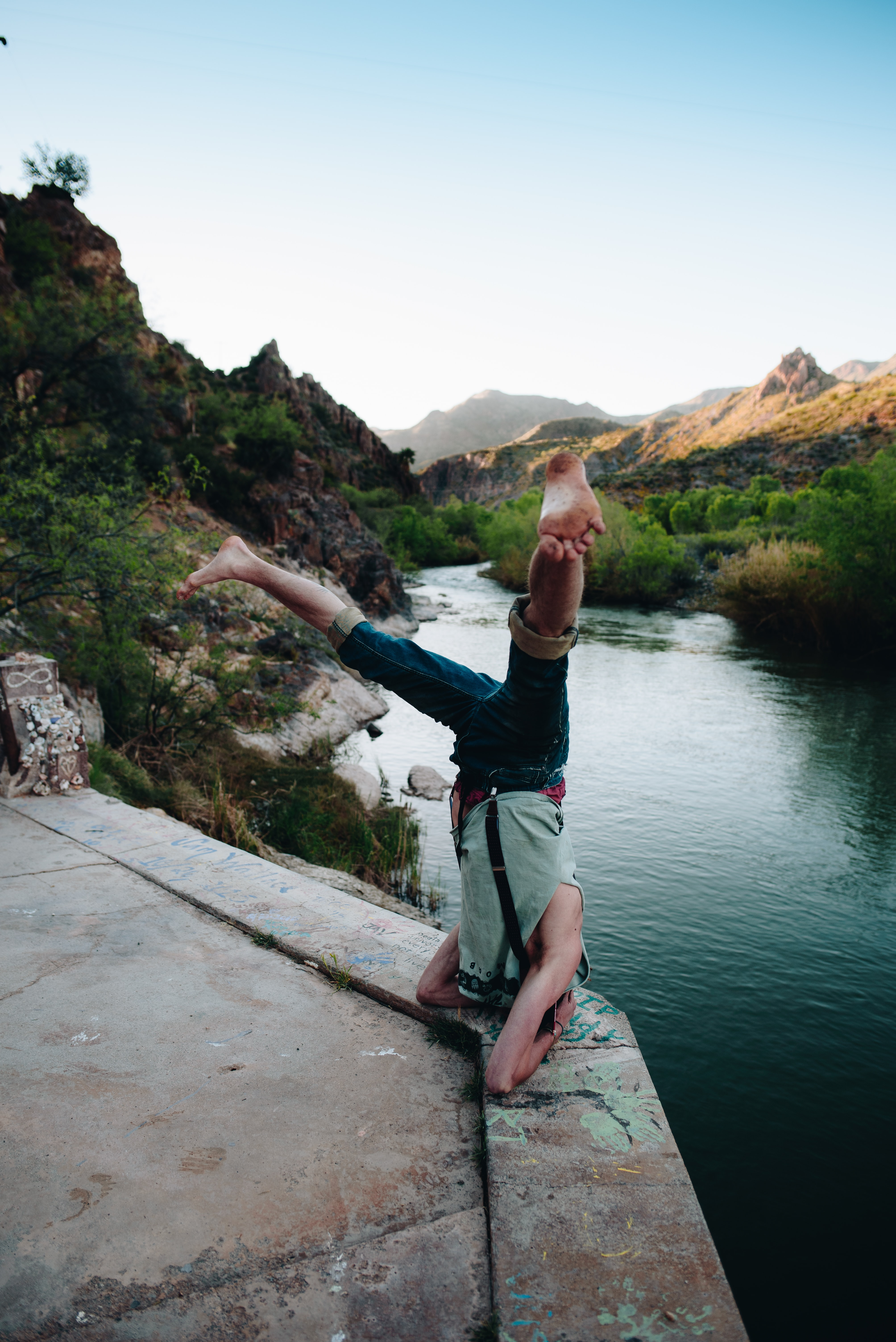 person in gray top doing headstand in front of body of water